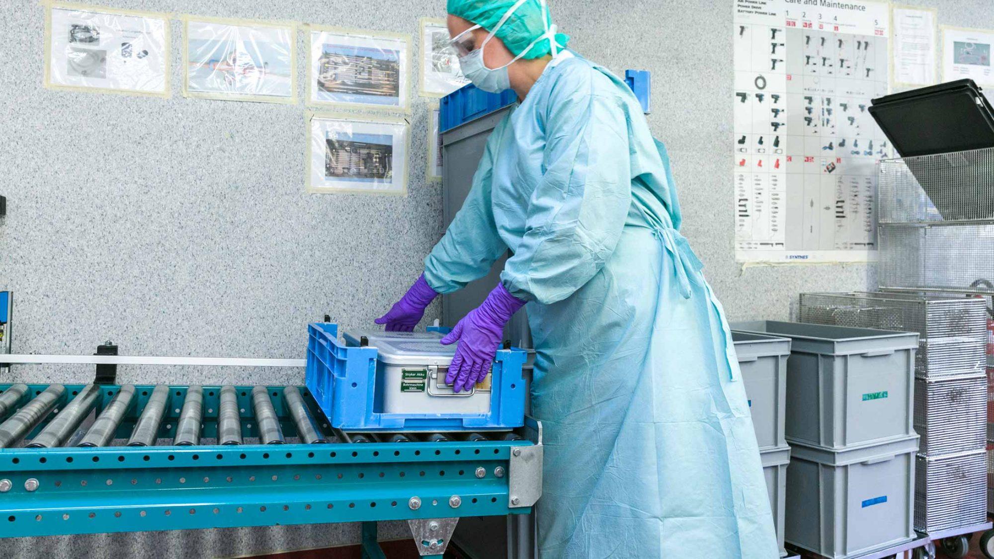 Die gebrauchten Instrumente kommen in der AEMP bei der Sterilisationsassistentin an.