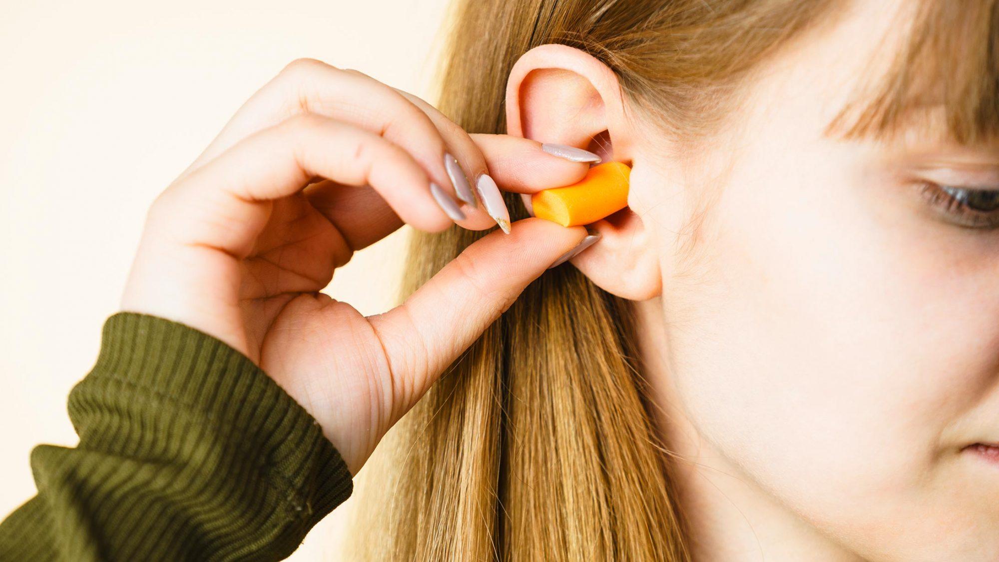 Eine junge Frau schützt Ihre Ohren mit Gehörschutzstöpsel
