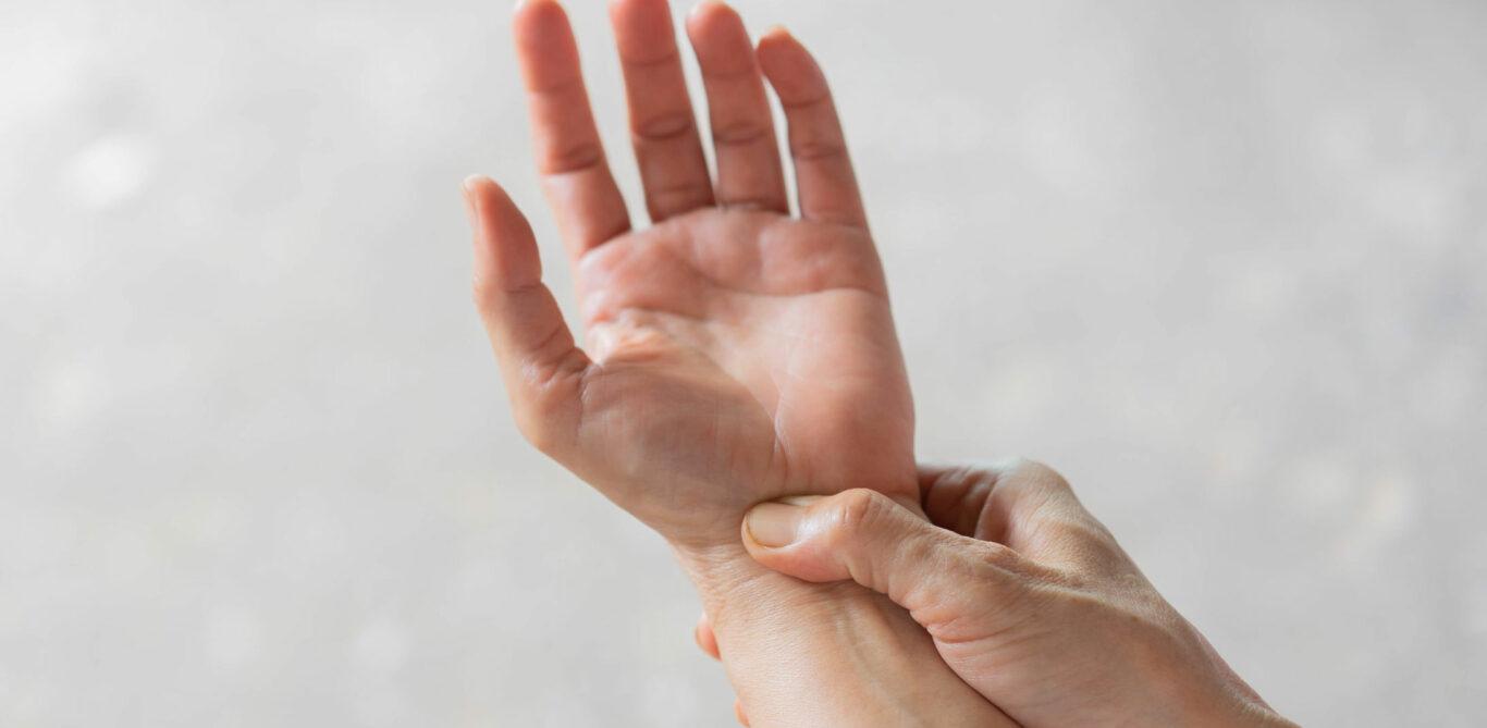 Das Bild zeigt zwei Hände, eine zeigt mit der Handfläche nach oben, die andere fühlt mit dem Daumen das Handgelenk.