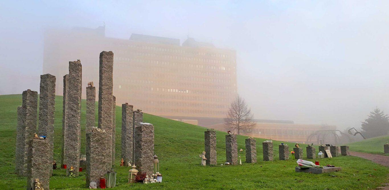 Totgeburt: Die Grabstätte für frühverlorene Kinder mit dem KSB-Gebäude im Nebel dahinter