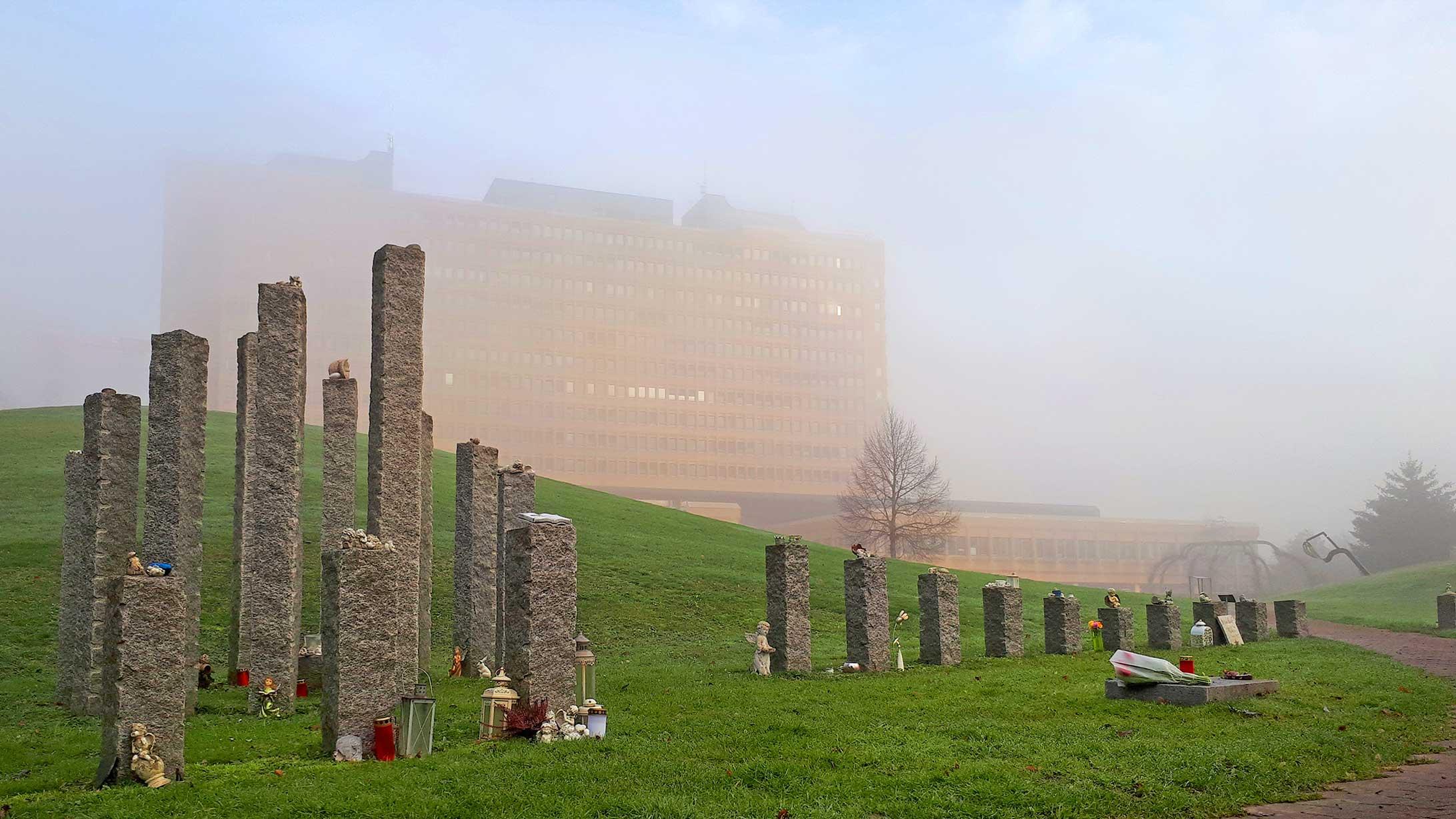 Die Grabstätte für frühverlorene Kinder mit dem KSB-Gebäude im Nebel dahinter