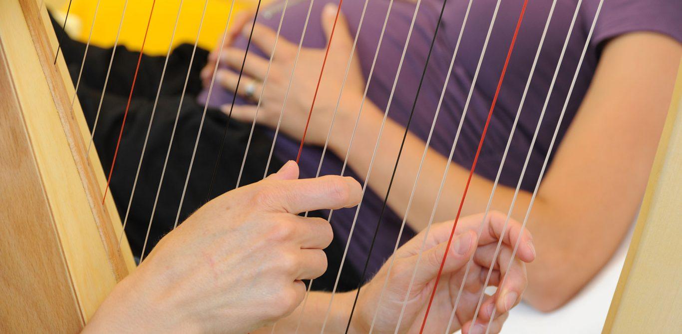 Musiktherapie: Renate Nussberger spielt einer schwangeren Patientin auf der Harfe vor.
