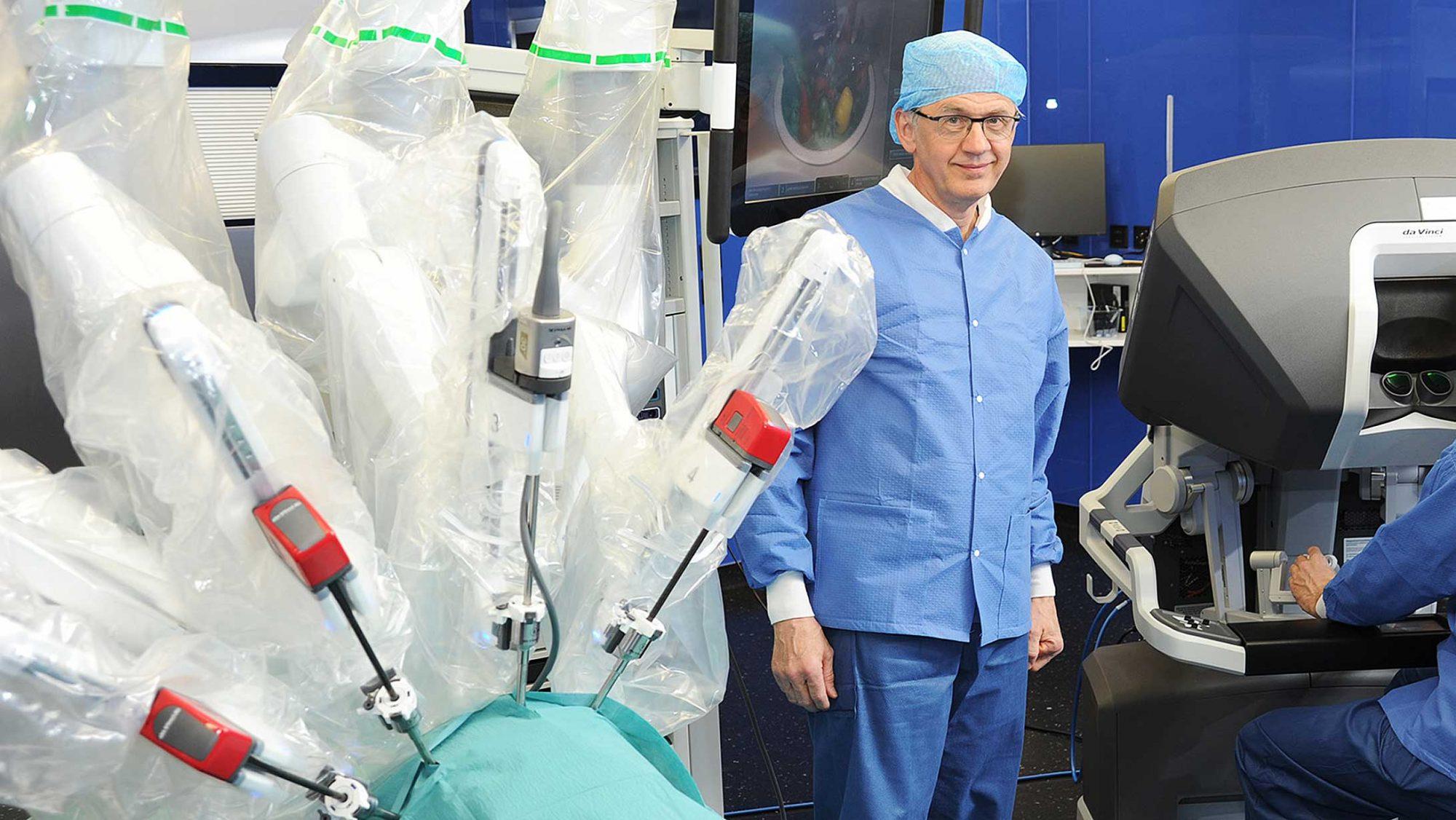 Dr. Kurt Lehmann steht neben dem Operationsroboter Da Vinci.
