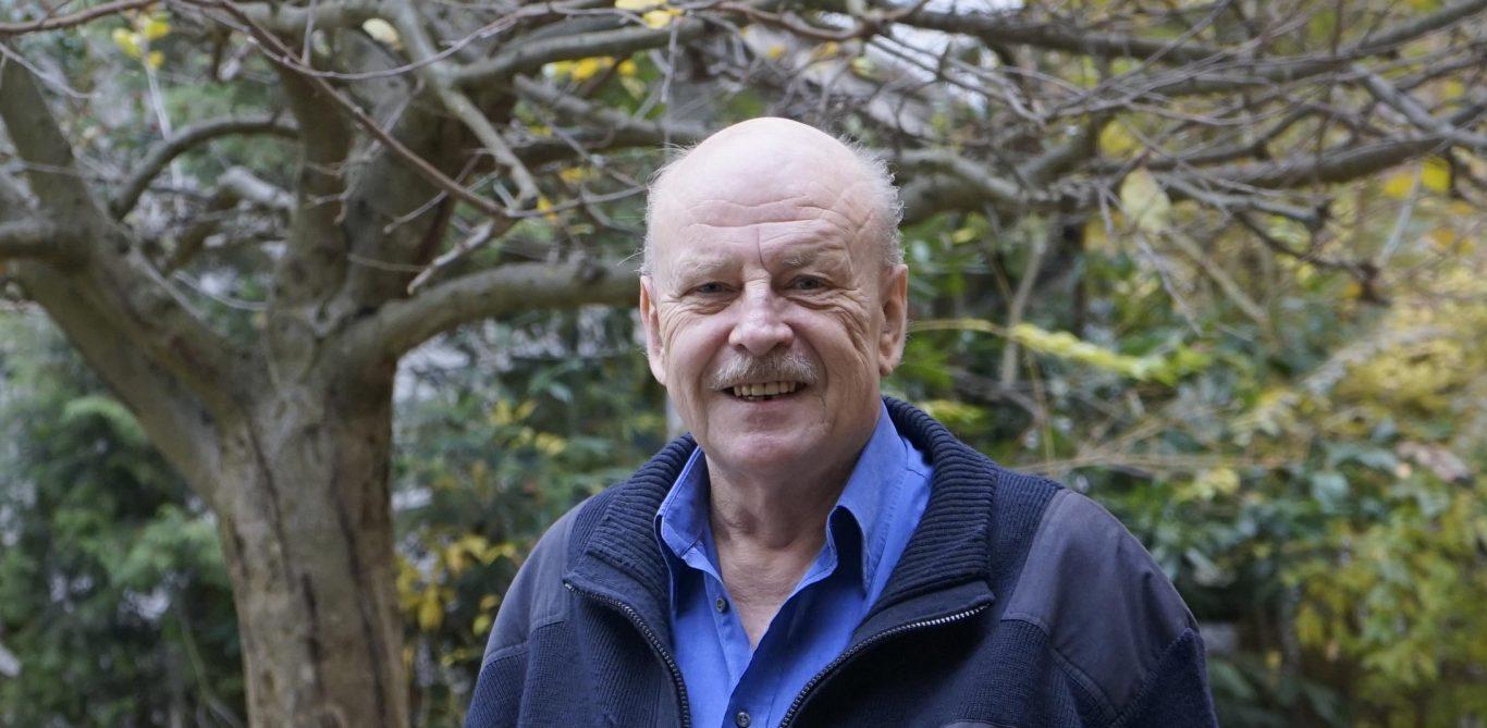Beat Huber steht draussen vor einem Baum. Er erzählt von seinen Erfahrungen mit PAVK.