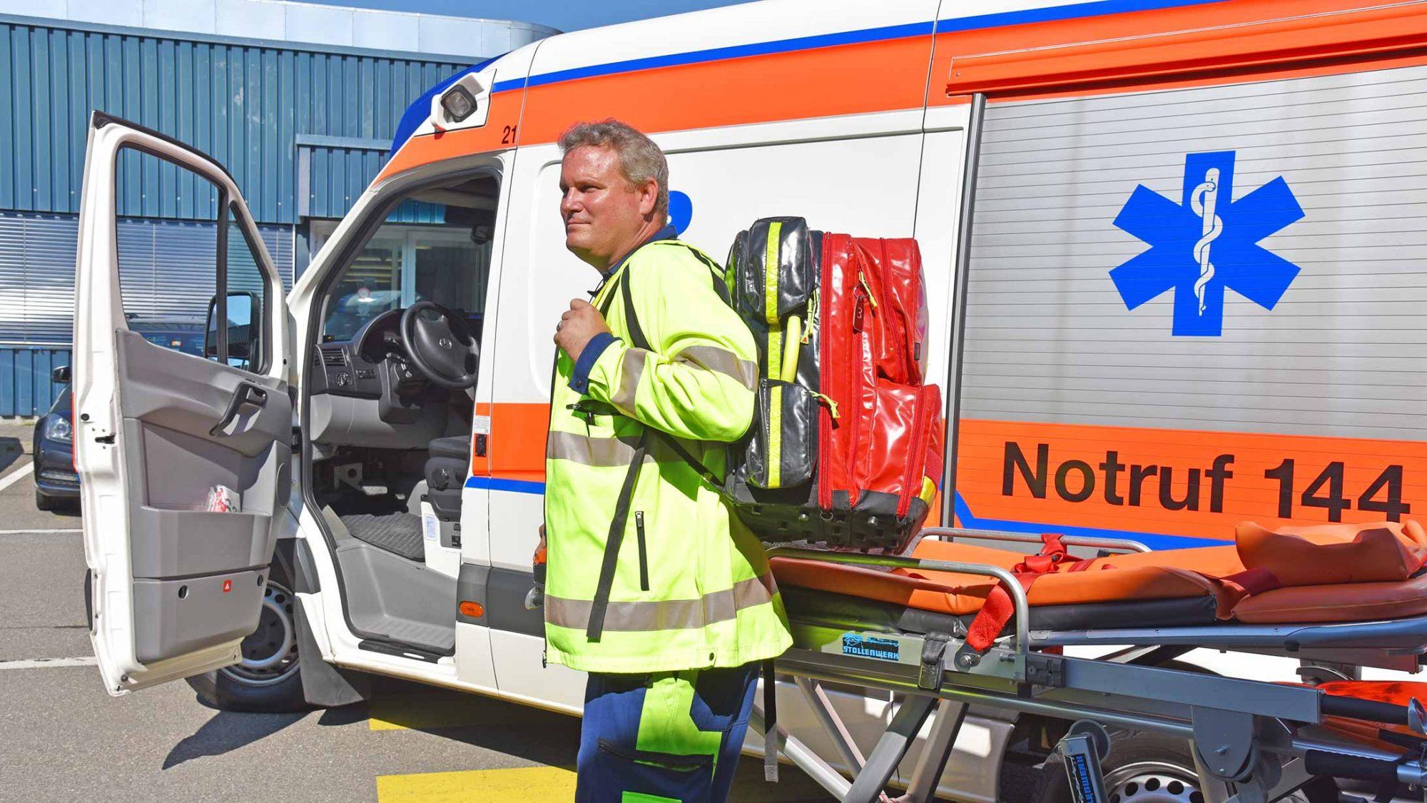 Rettungssanitäter Lukas Frey mit seinen Arbeitsutensilien vor dem Ambulanzfahrzeug