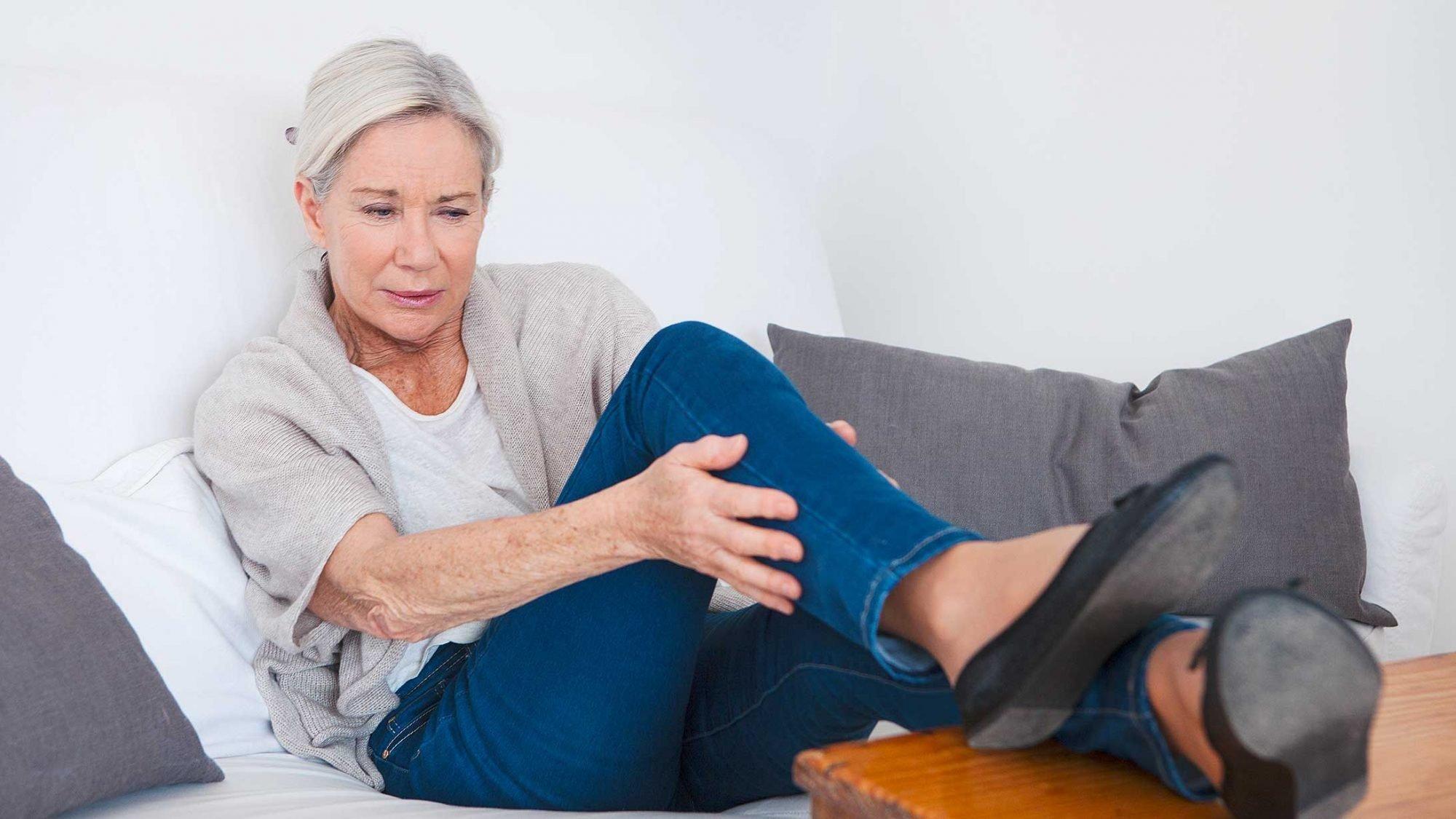 Raucherbein: Eine Frau hält ihr schmerzendes Bein.