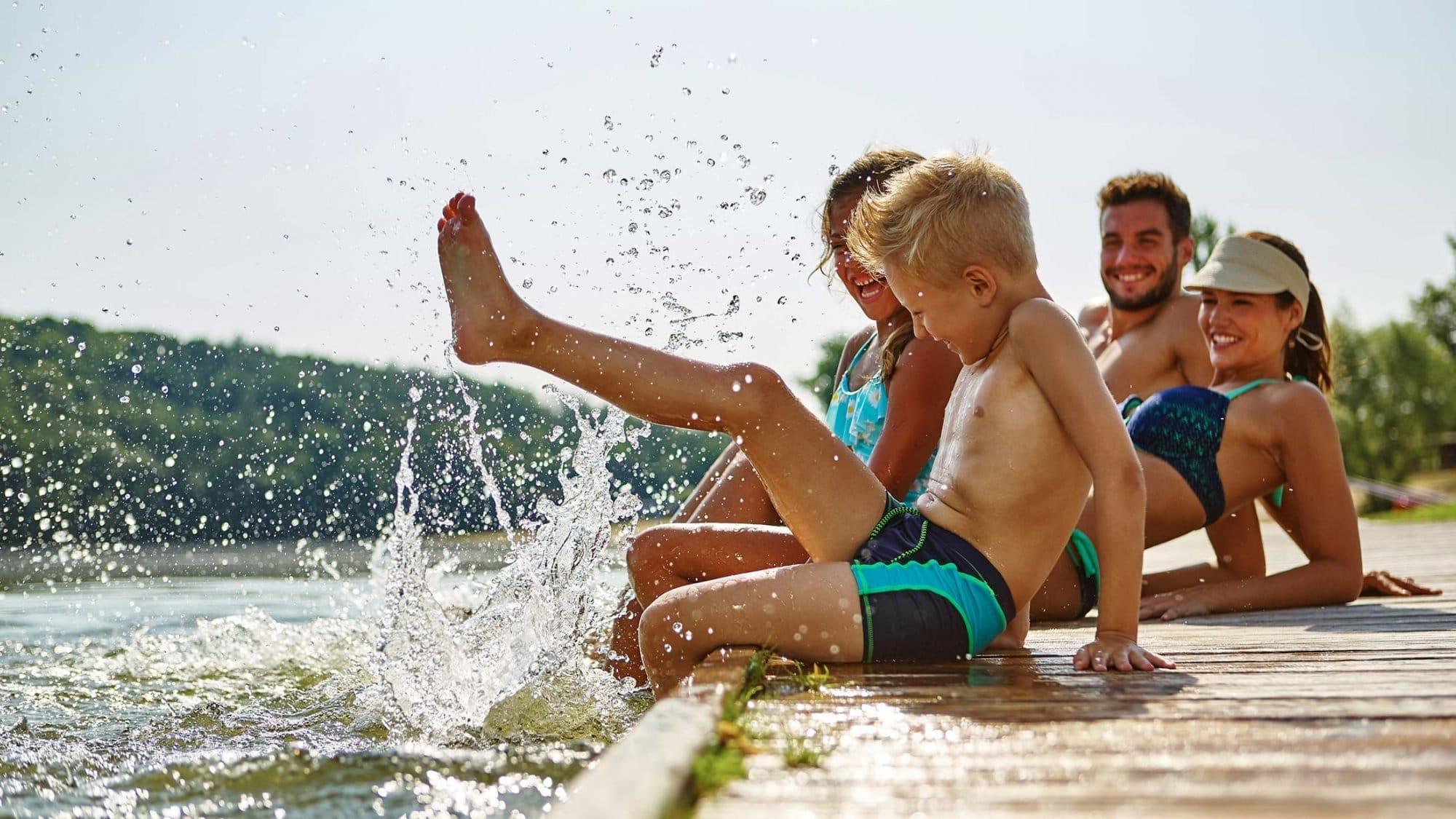 Eine Familie liegt am Wasser