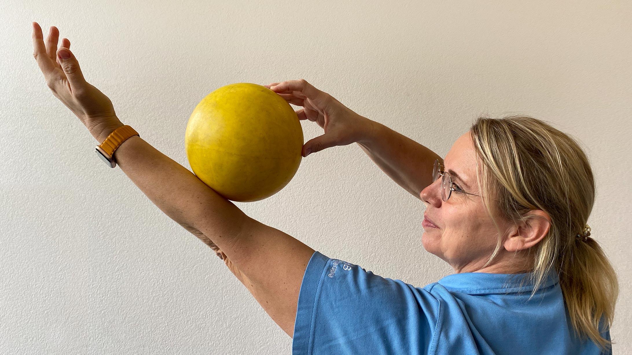 Physiotherapeutin Monika Loebel rollt sich einen gelben Ball über den ausgestreckten Arm.