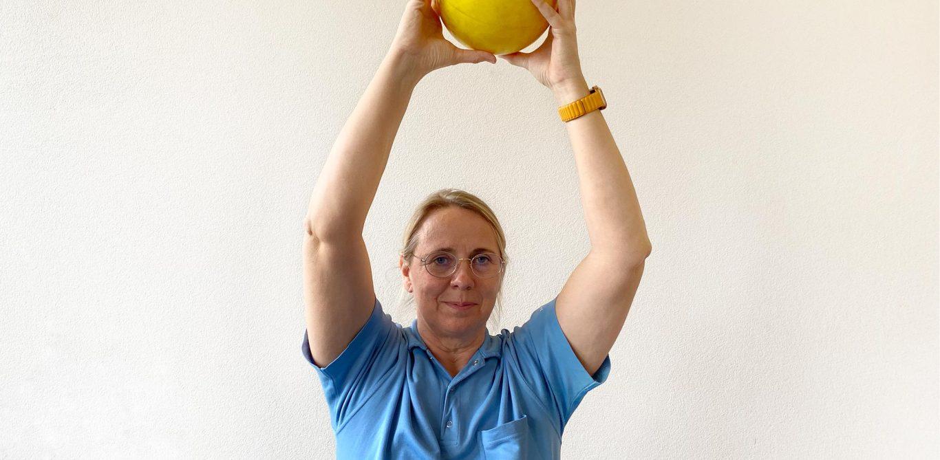 Physiotherapeutin Monika Loebel trainiert mit einem gelben Ball.