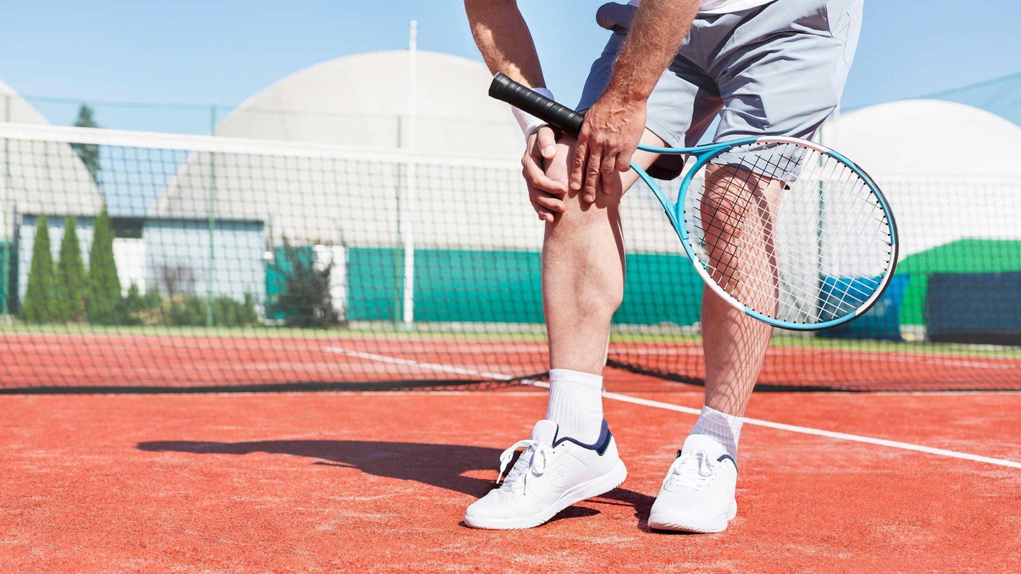 Ein Tennisspieler hält sich das schmerzende Knie.