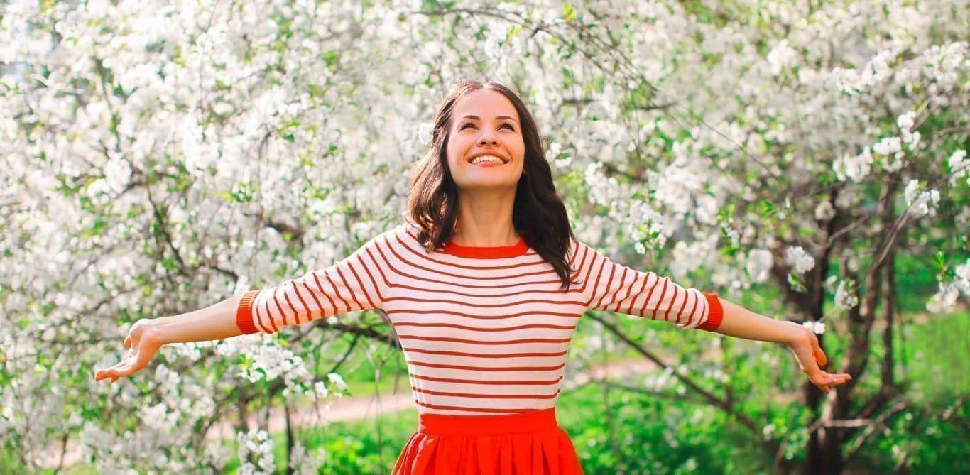 Mit gesunden Lebensmitteln schlank in den Frühling: Eine Frau auf einer Wiese.