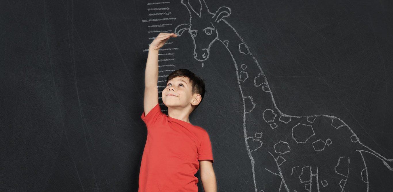Ein Junge misst sein Wachstum an einer Tafel