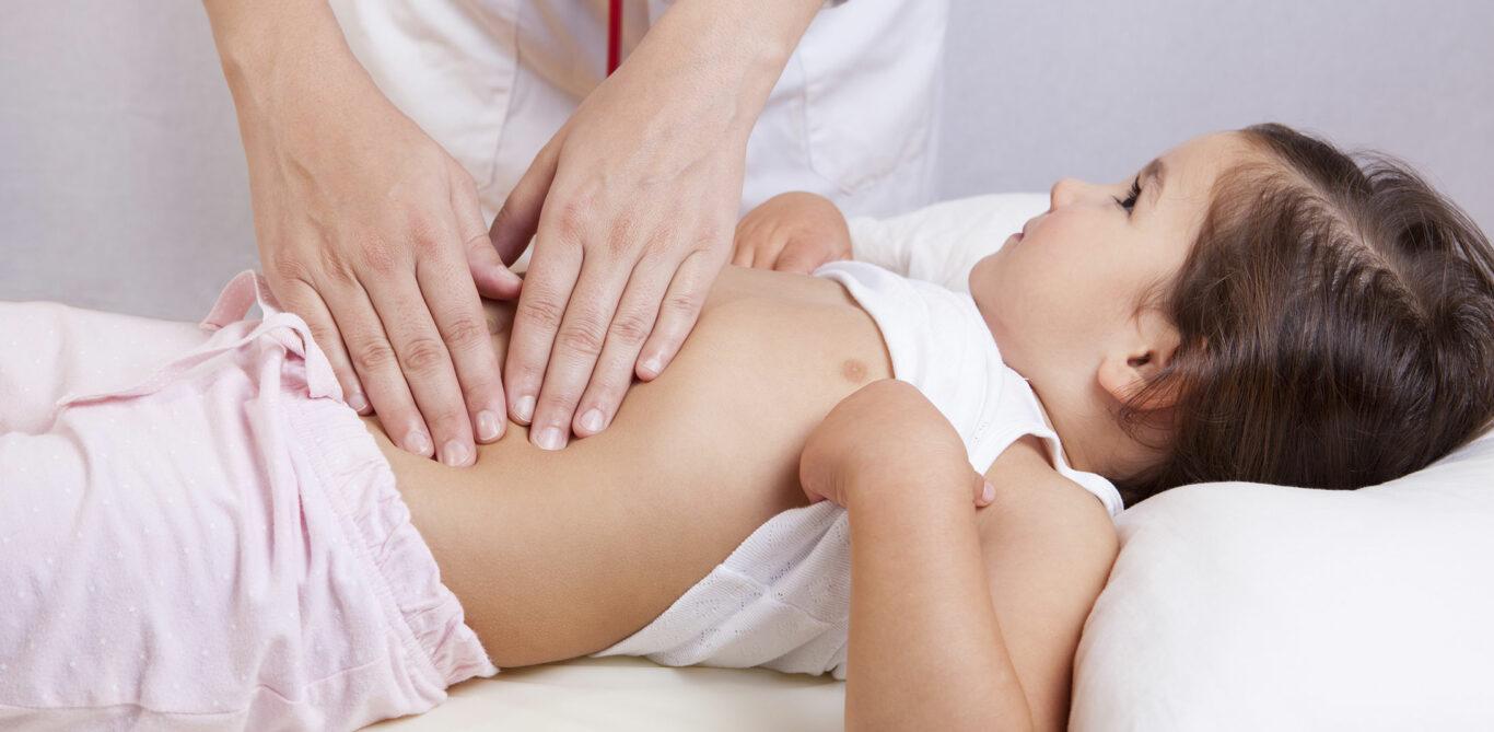Ein Arzt tastet den Bauch eines Kindes ab.