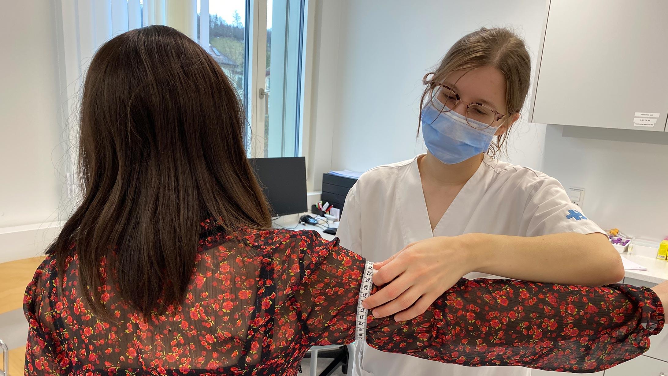 Eine Ärztin misst den Umfang des Oberarmes der Patientin.