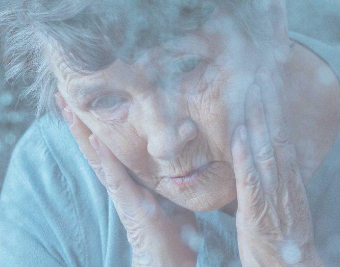 Eine ältere Frau stützt den Kopf auf ihren Händen auf.