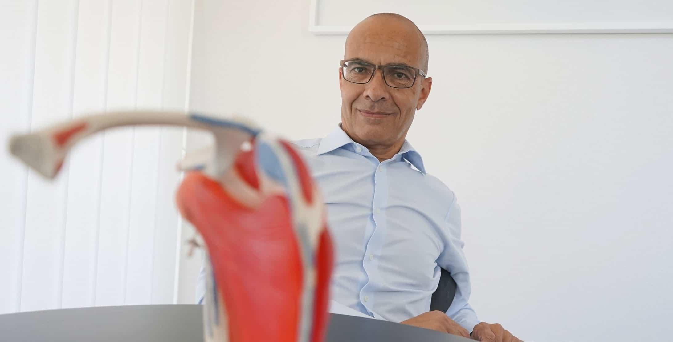 Portrait von Karim Eid mit einem Modell eines Schultergelenks