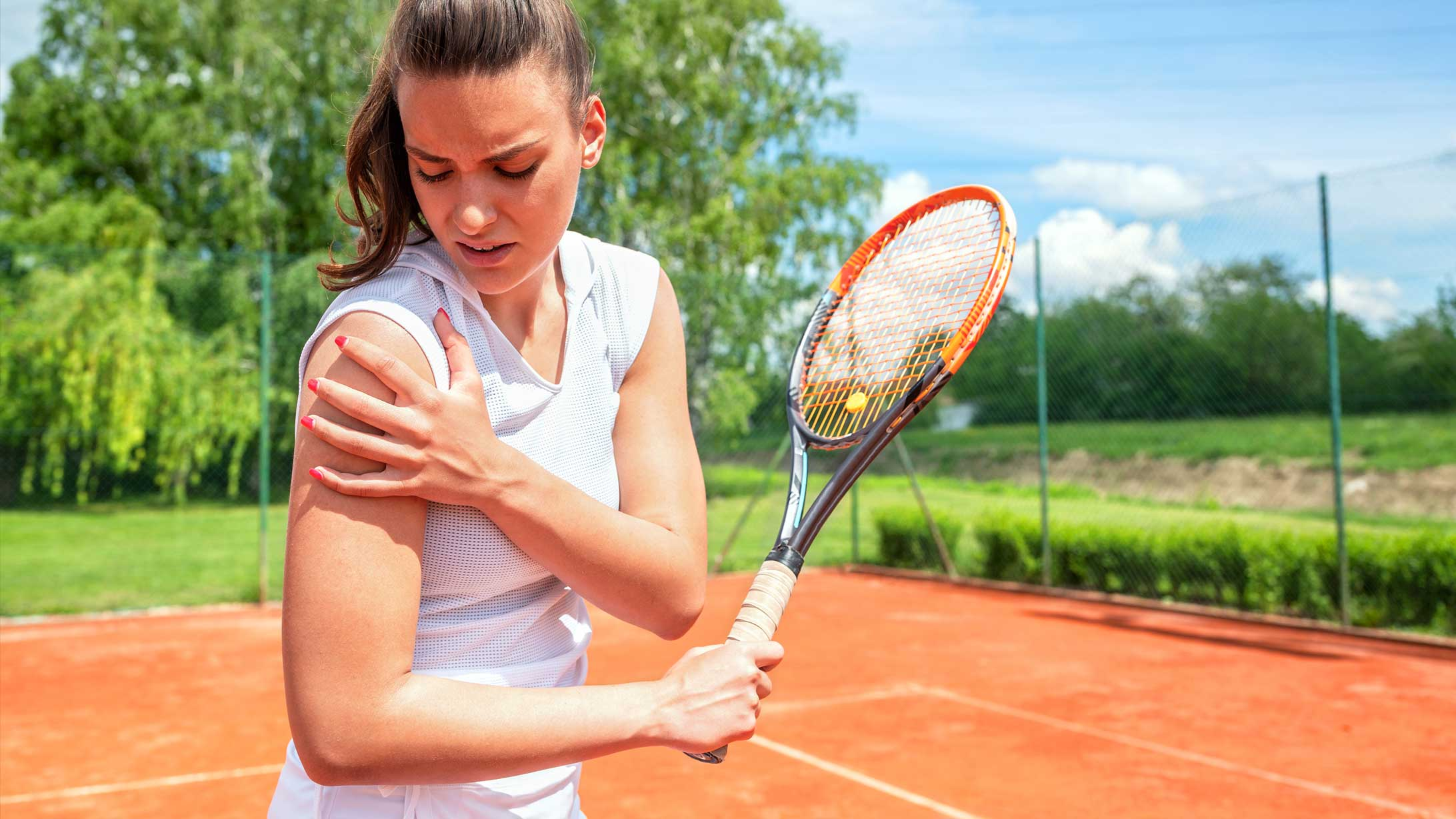 Frau die Tennis spielt hält sich die Schmerzende Schulter