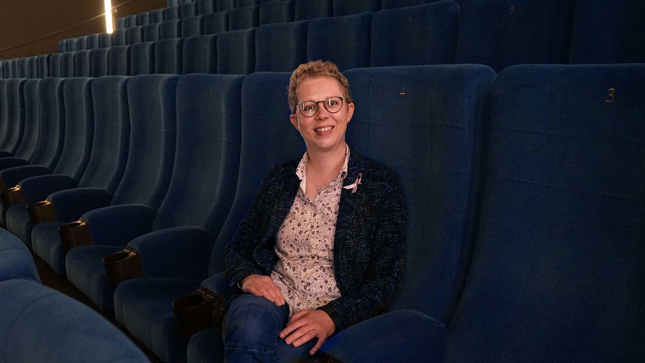 Alexandra Sterk, Brustkrebspatientin und Kinobesitzerin, sitzt im leeren Kinosaal.