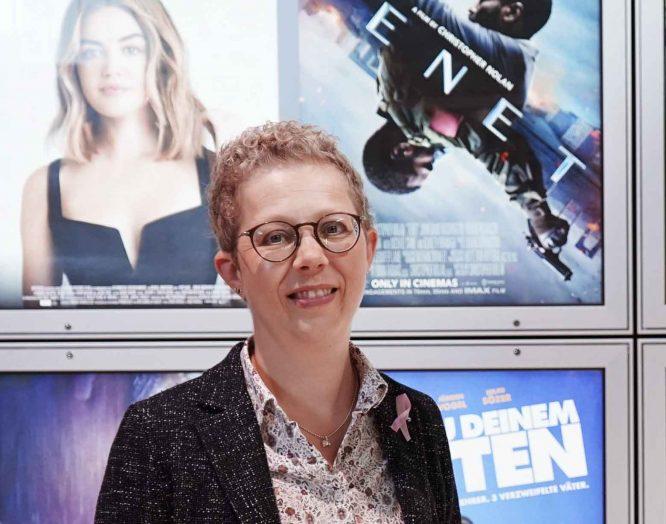 Alexandra Sterk, die an Brustkrebs erkrankte, steht in ihrem Kino vor den Plakaten der aktuellen Filmen.
