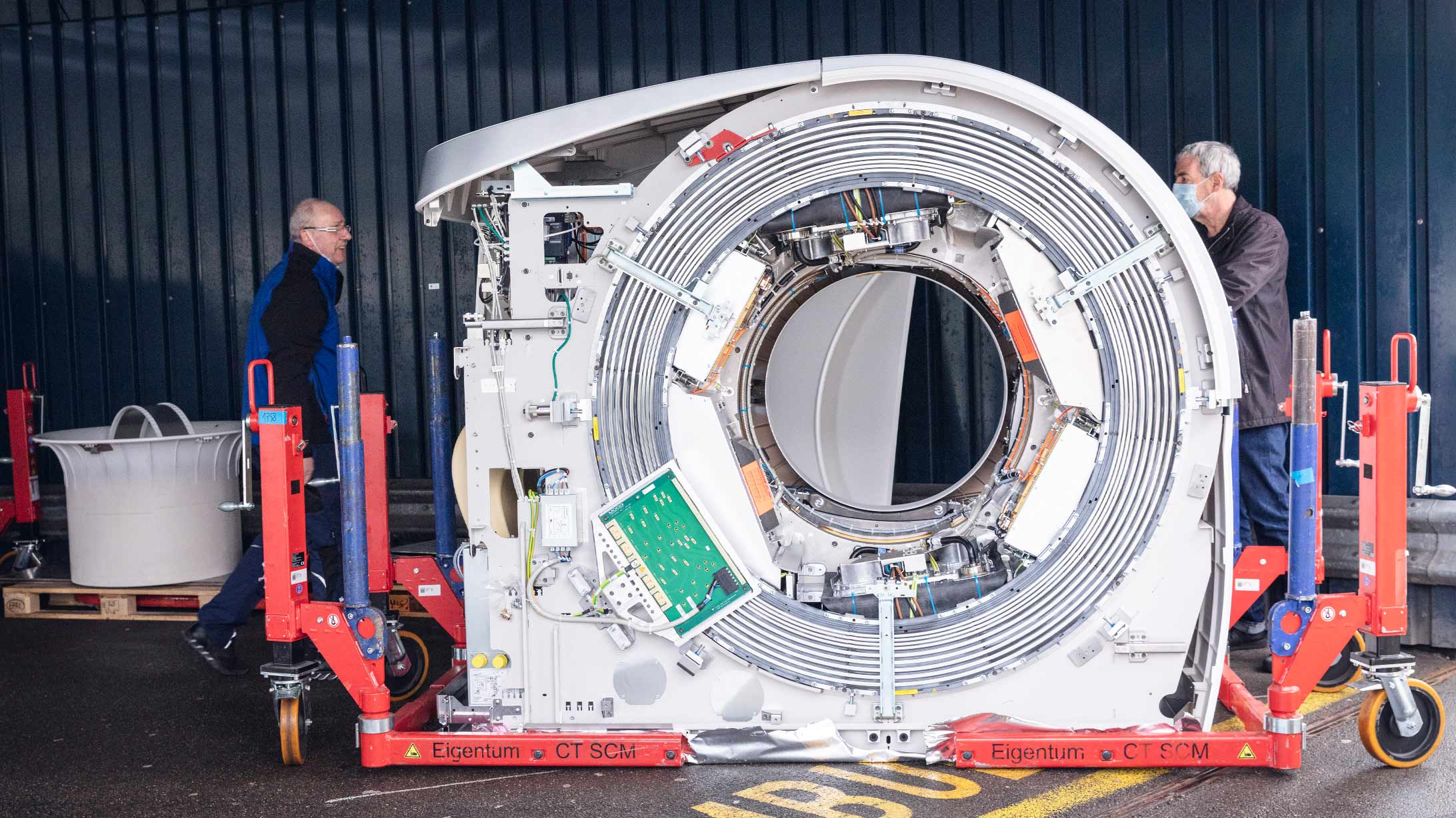 Zwei Mitarbeiter liefern beim KSB ein Computertomographie-Gerät an. Die Haube ist entfernt, sodass die Elektronik im Inneren sichtbar wird.