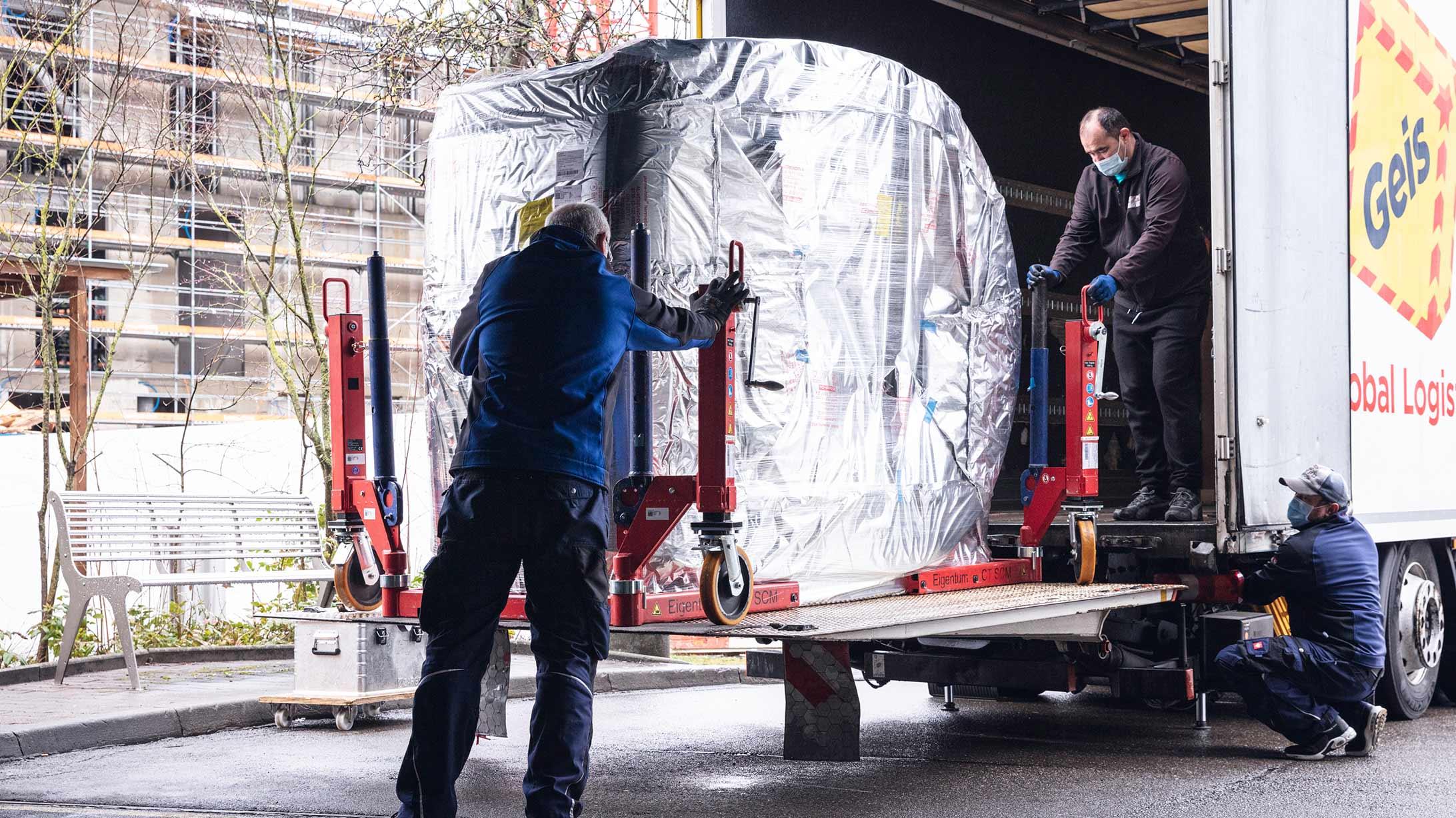 Männer laden ein CT-Gerät aus einem Lastwagen.