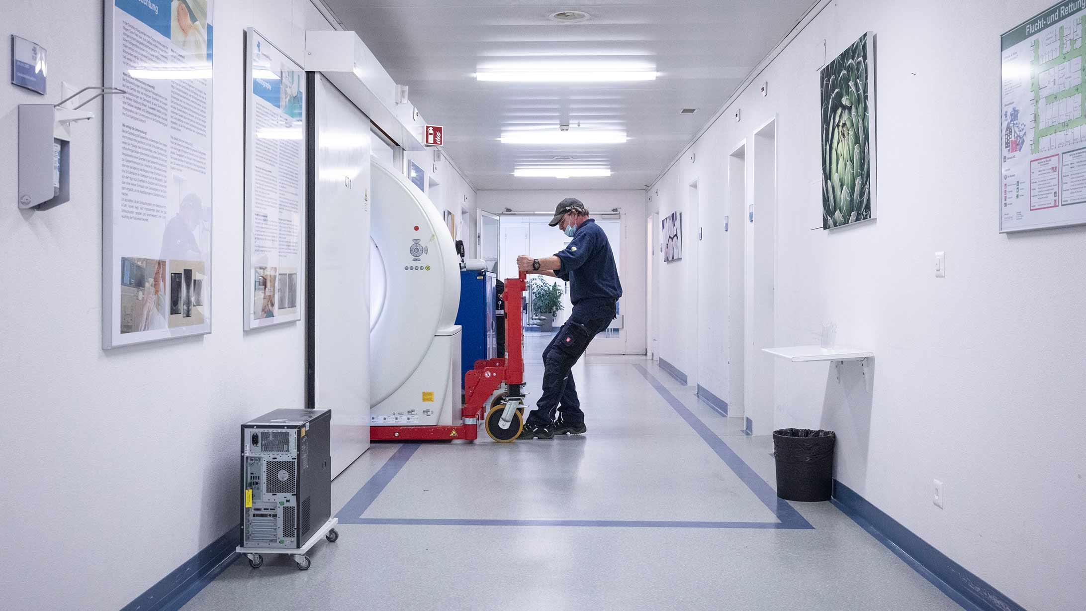 Anlieferung: Ein Mitarbeiter fährt mit dem neuen CT-Gerät des KSB vorsichtig durch eine Tür.