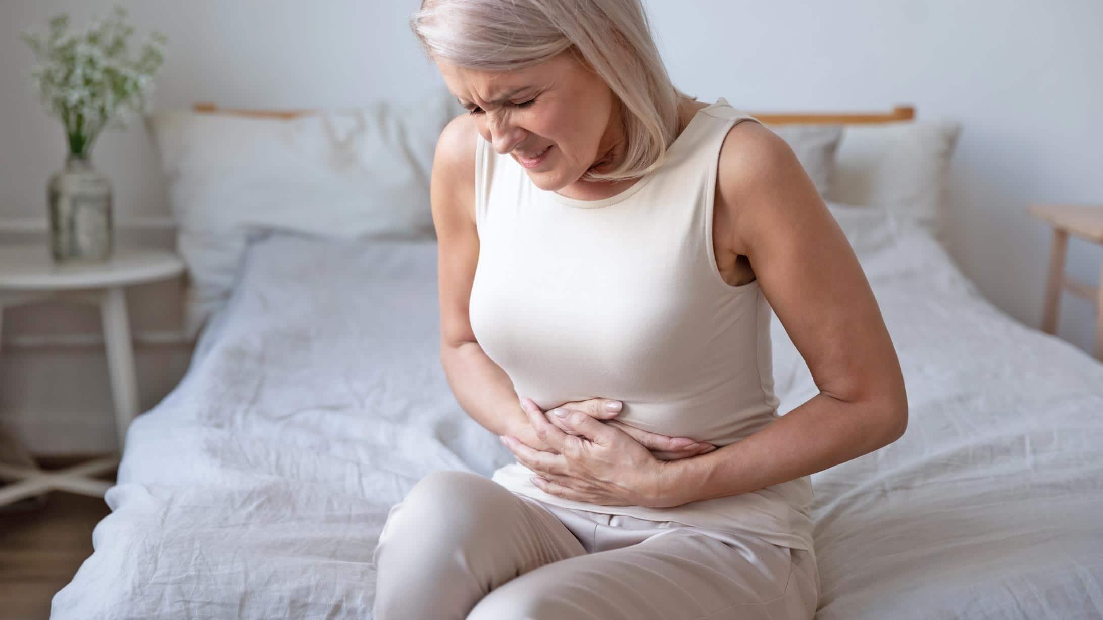 Eine Frau hält sich den schmerzenden Bauch