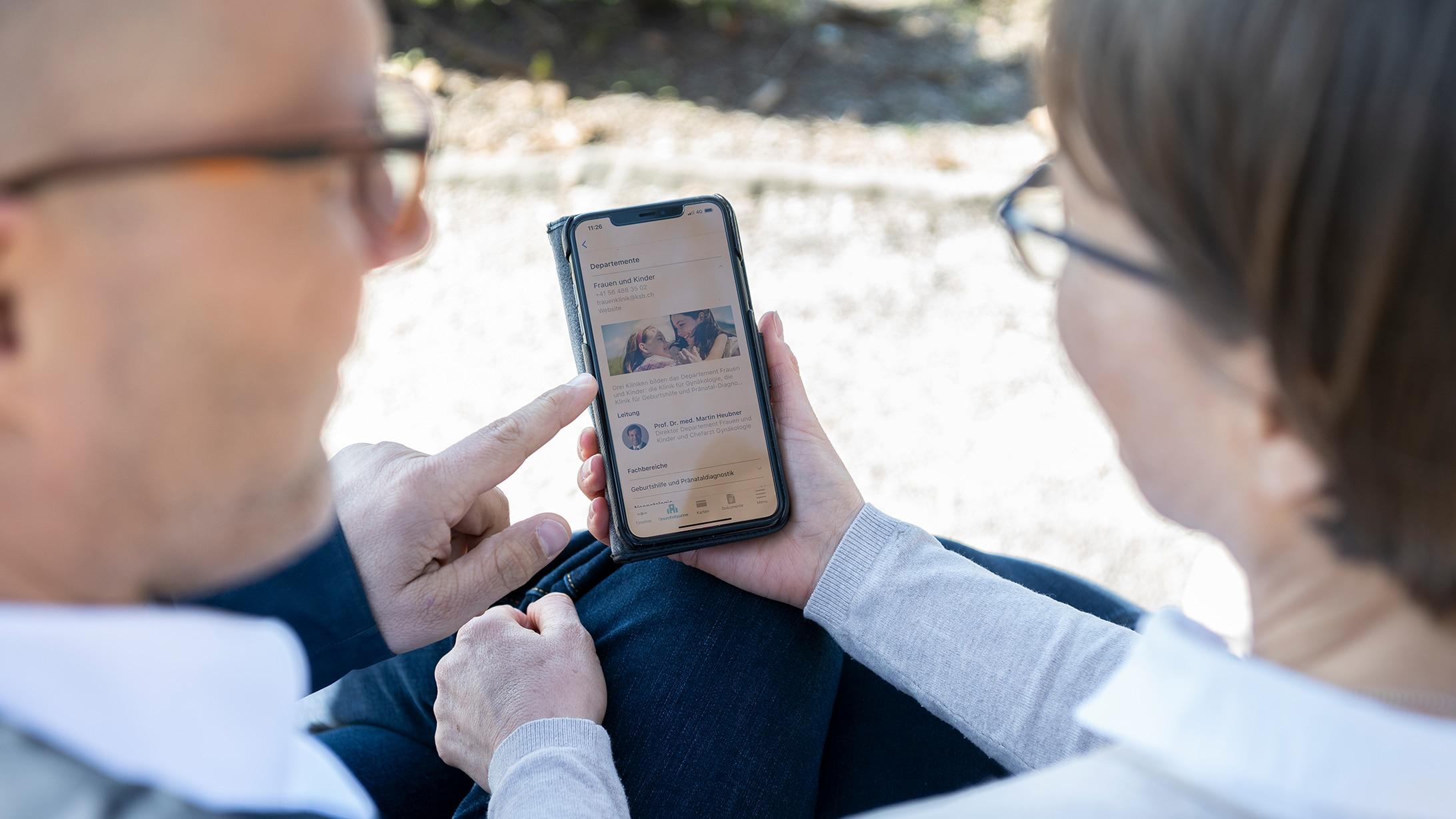 Zwei Personen schauen auf ein Smartphone mit der Hey Patient App und reden miteinander.