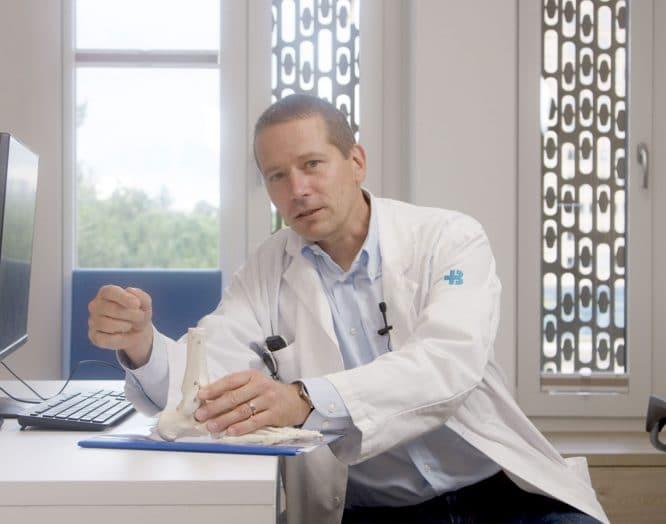 rs Neurauter, Leitender Arzt Orthopädie, sitzt im Sprechzimmer
