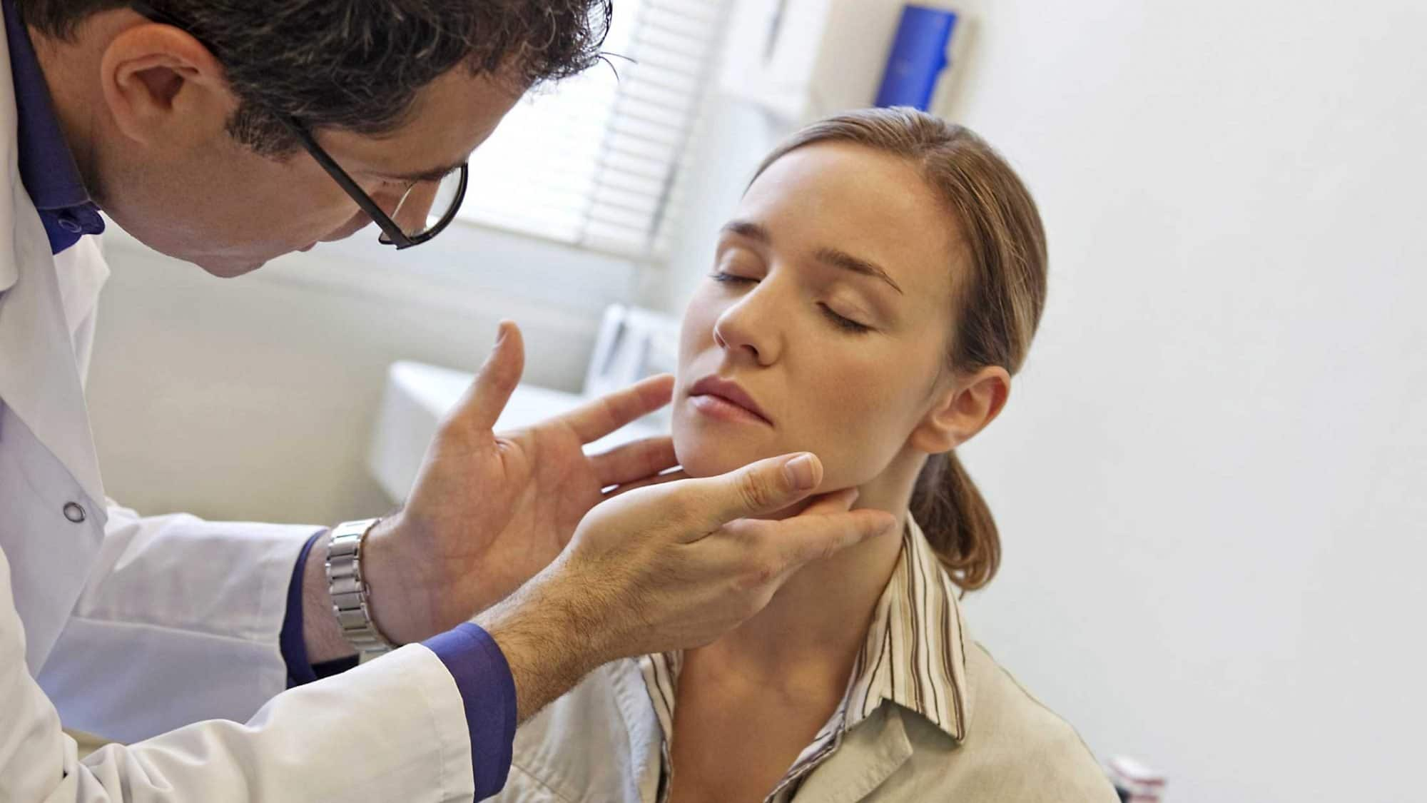 Ein Arzt tastet die Lymphknoten einer Patientin ab