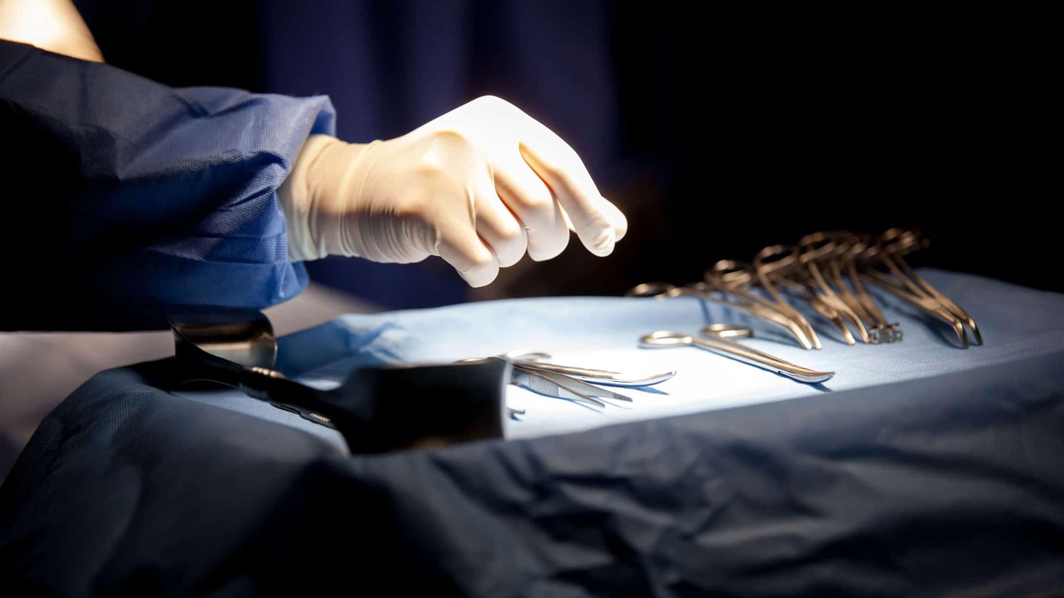 Ein Chirurg greift während einer Hysterektomie nach dem Skalpell.