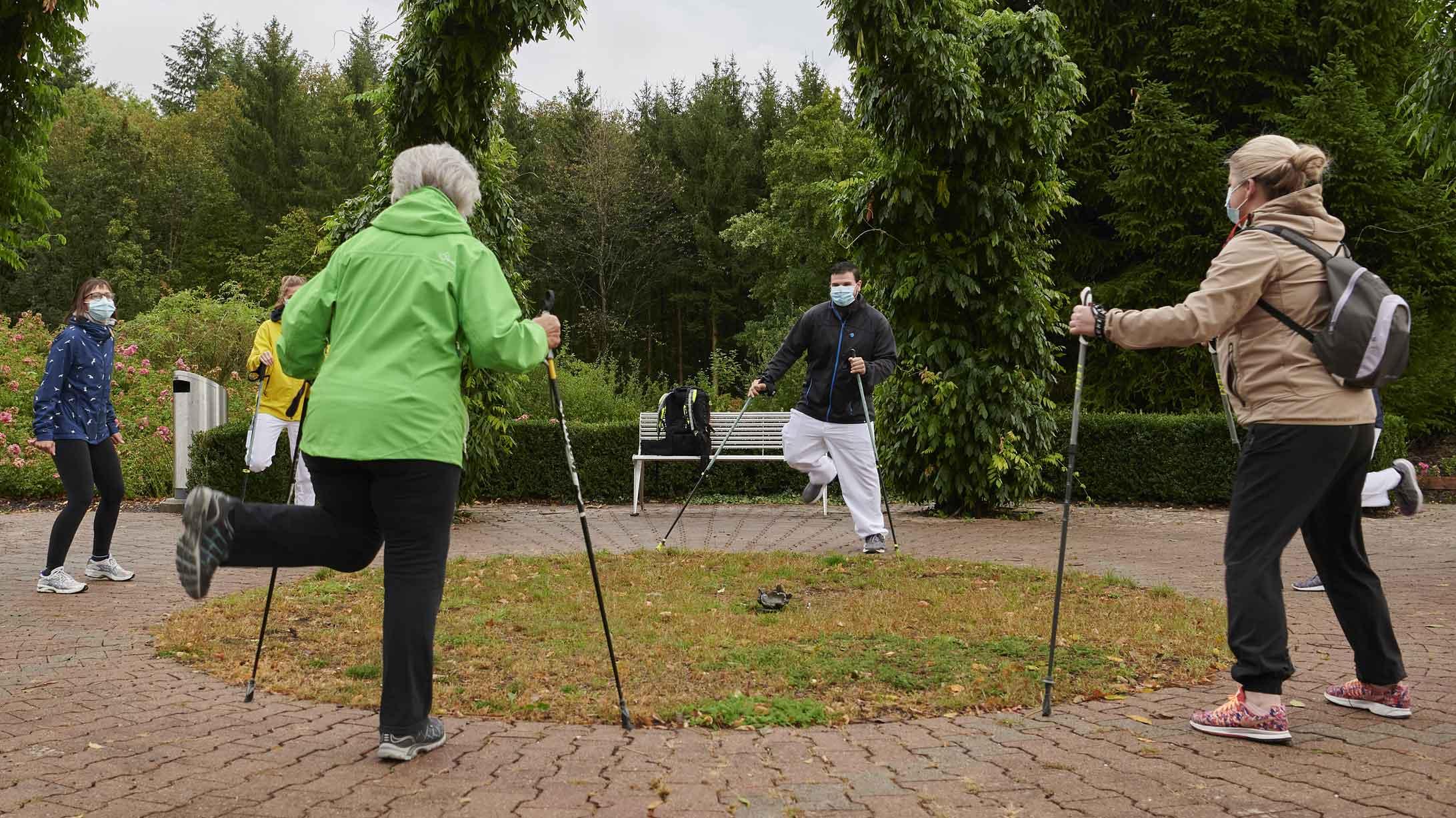 Ein Physiotherapeut leitet eine Gruppe beim Aufwärmen für Nordic Walking an.