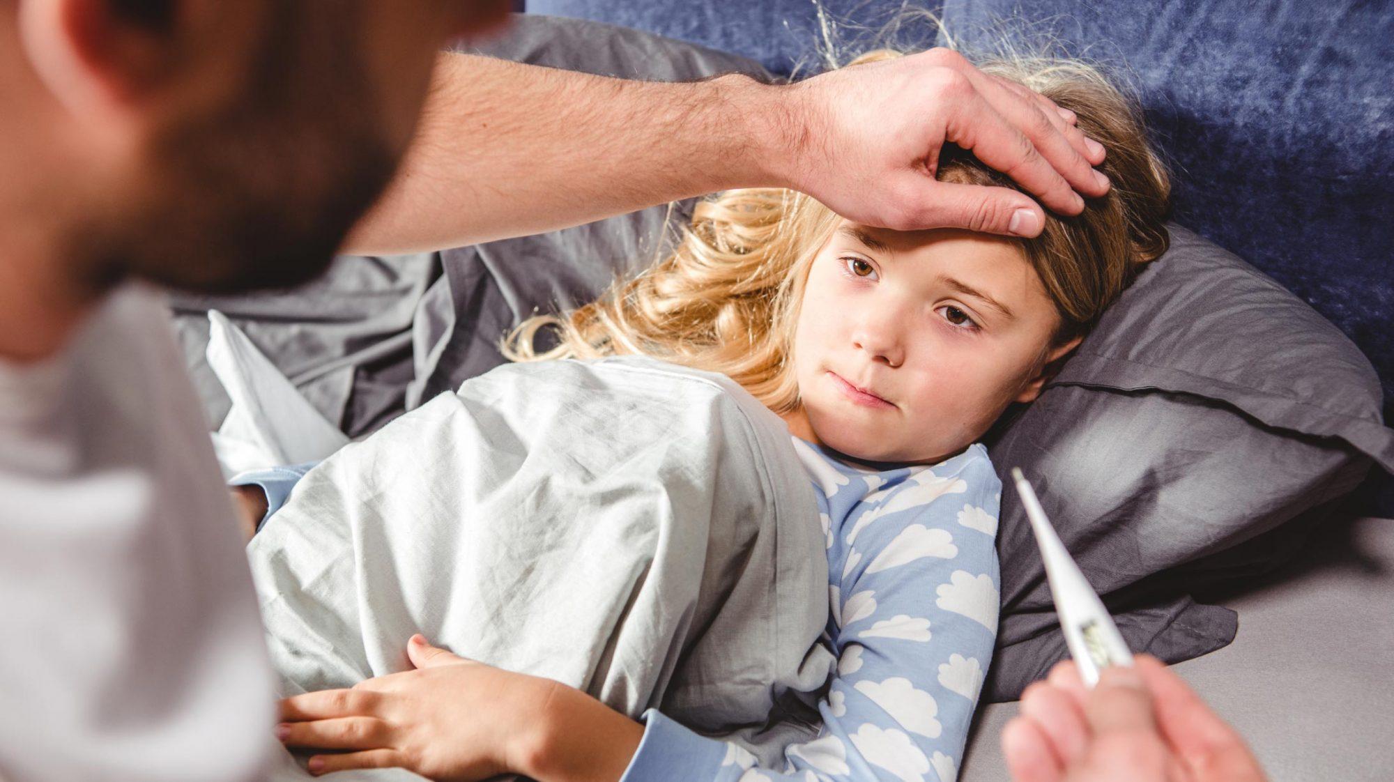 Ein Kind mit Fieber und Mittelohrentzündung im Bett