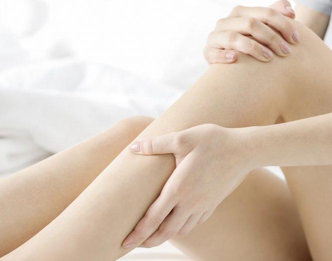 Frau hält sich die Beine. Ein Kribbeln ist typisch für das Restless-Legs-Syndrom.