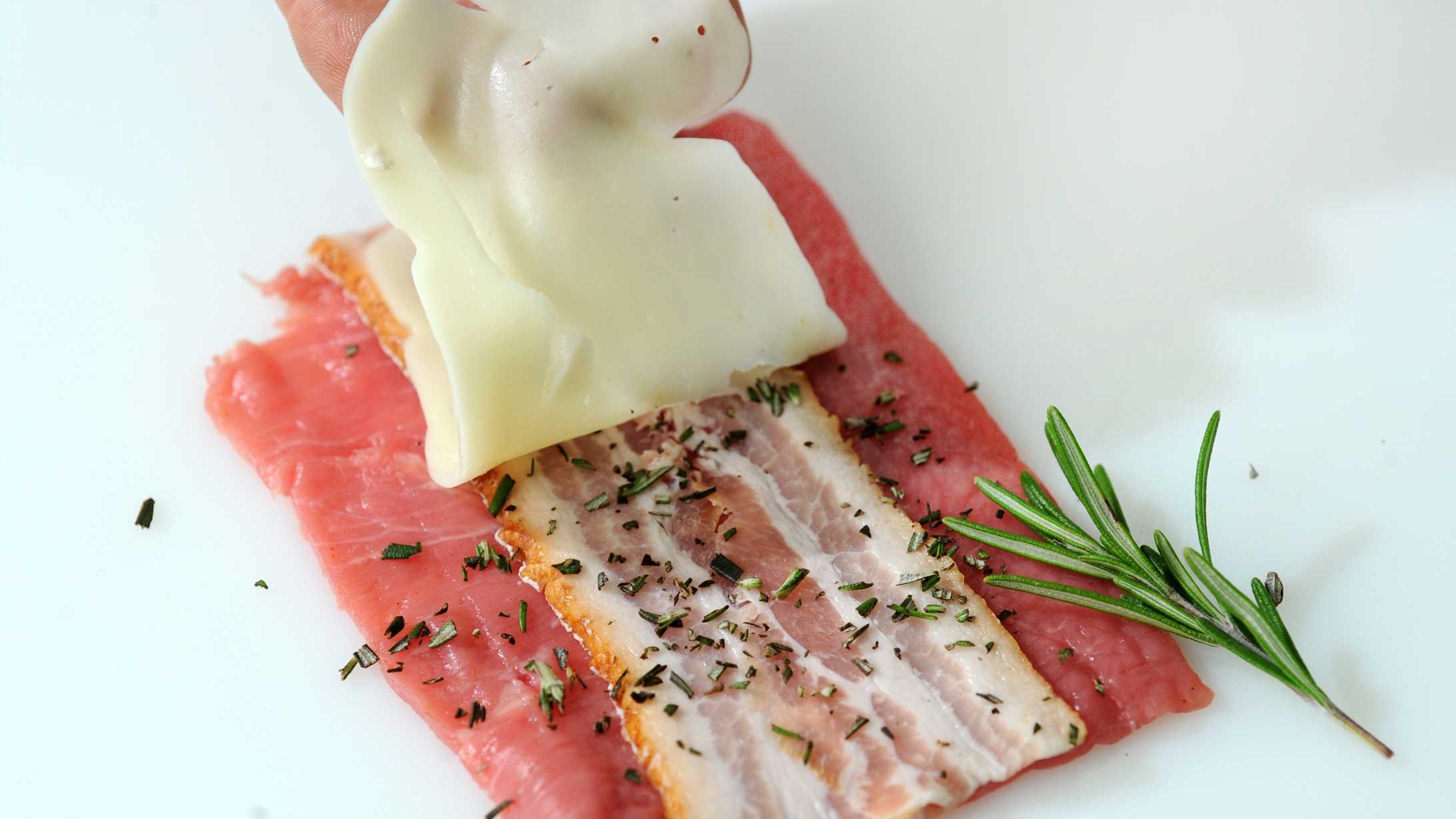 Kalbsfleisch. wird mit Speck und Käse belegt.