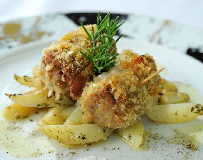 Apulische Kalbfleischröllchen mit Kartoffeln auf einem Teller