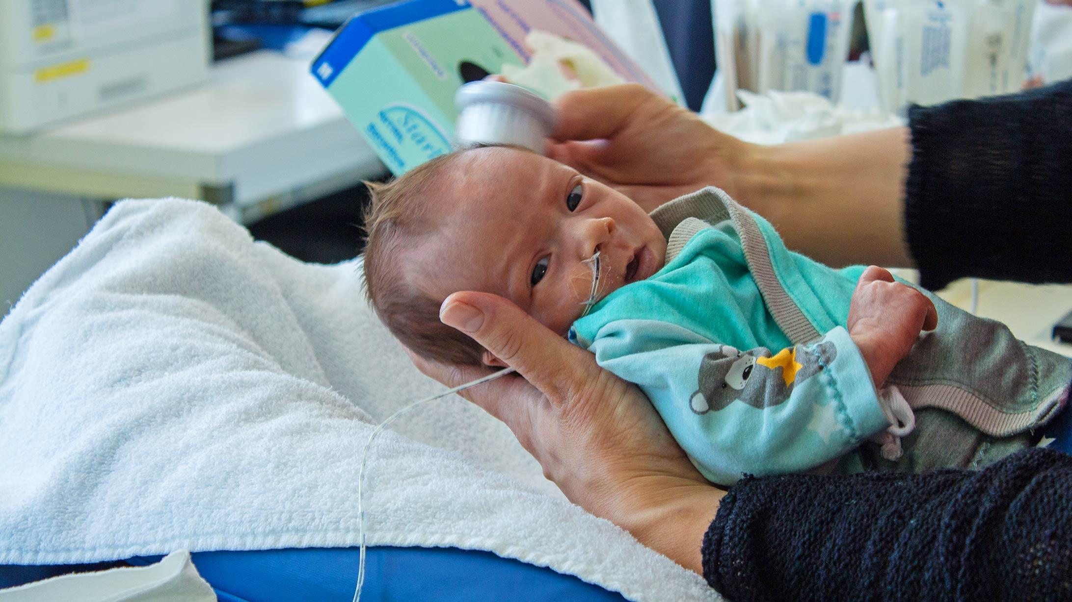 Ein Baby wird mit einer kleinen Haarbürste gebürstet.