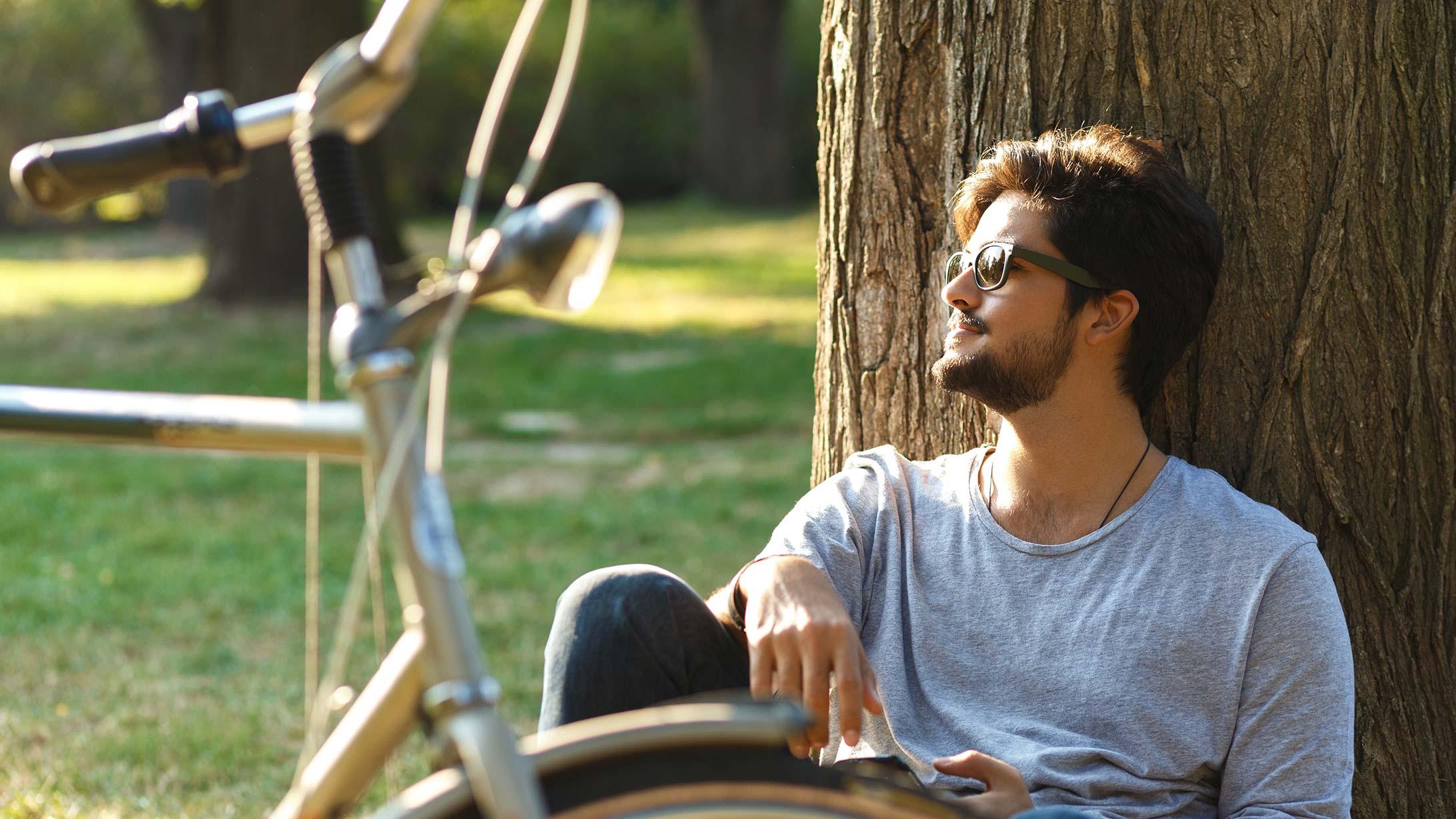 Ein Mann mit Sonnenbrille lehnt an einem Baum