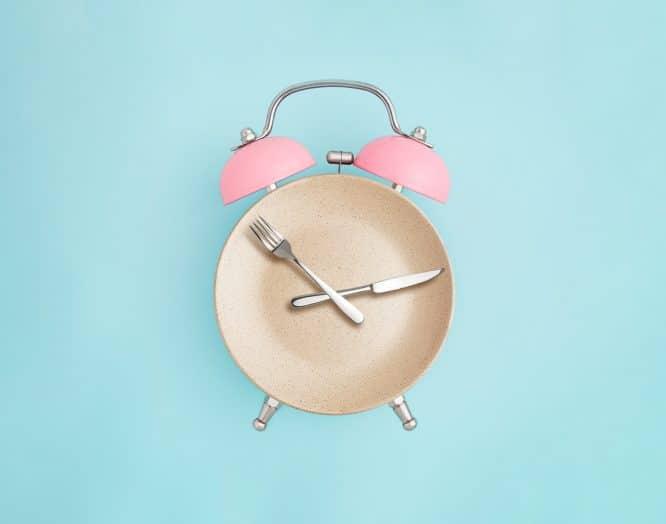 Ein Wecker aus einem Teller und Besteck als Symbolbild für Intervallfasten