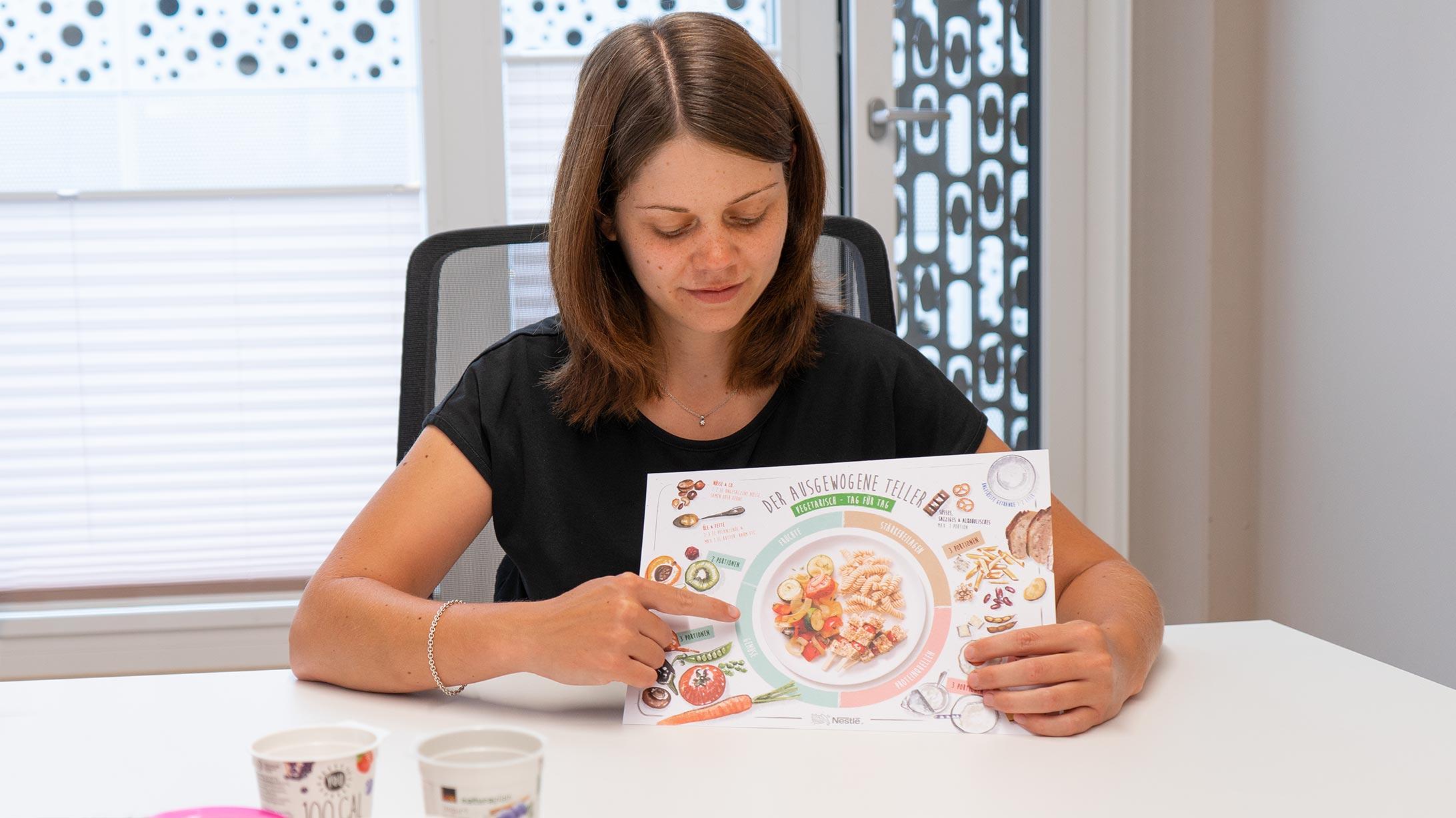 Ernährungsberaterin Nadja Greub mit Lebensmitteln und einem Schaubild zur gesunden Ernährung
