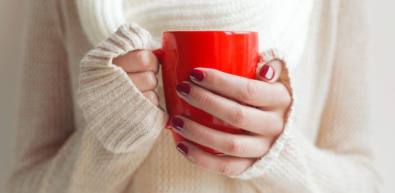 Eine Frau mit kalten Händen hält eine Tasse