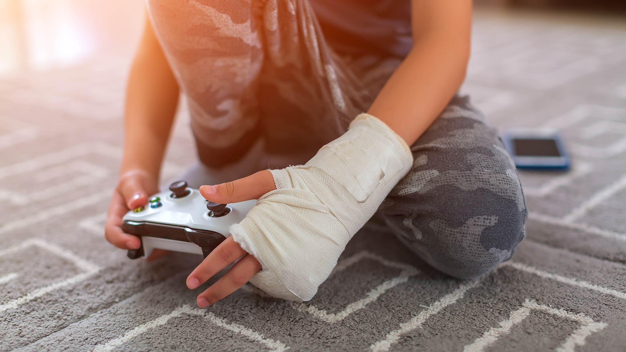 Ein Junge mit gegipstem Arm beim Gamen.