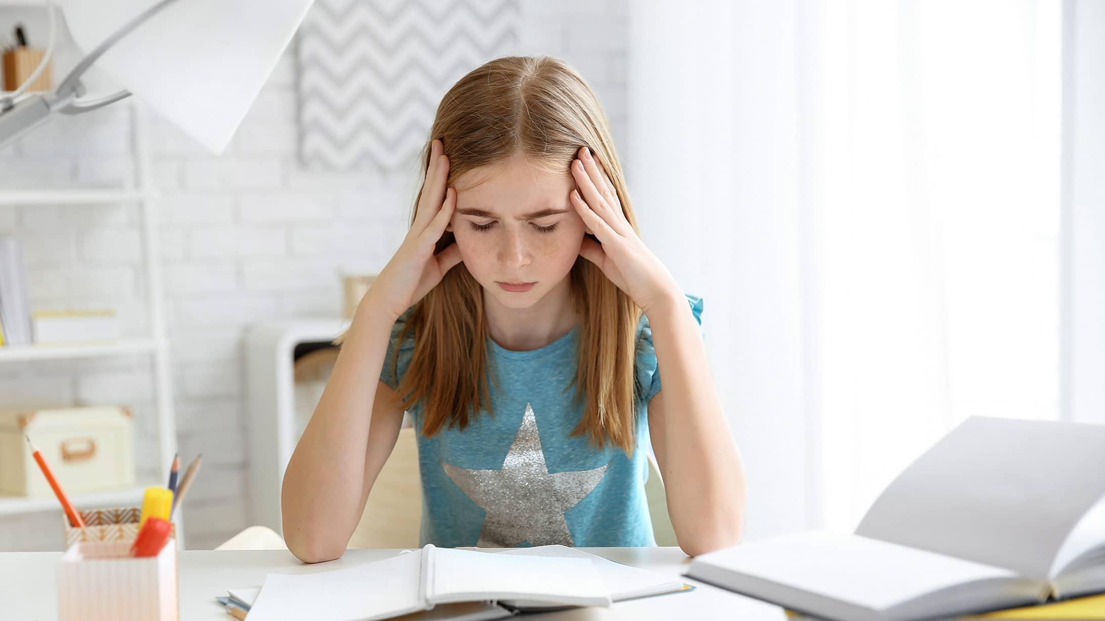 Mädchen mit Kopfschmerzen während der Hausaufgaben.