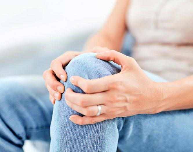 Eine Frau hält sich ihr Knie wegen Knieschmerzen.