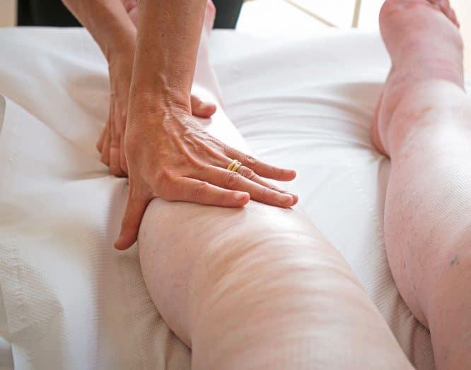 Eine Frau untersucht die Beine einer Patientin mit Lipödem