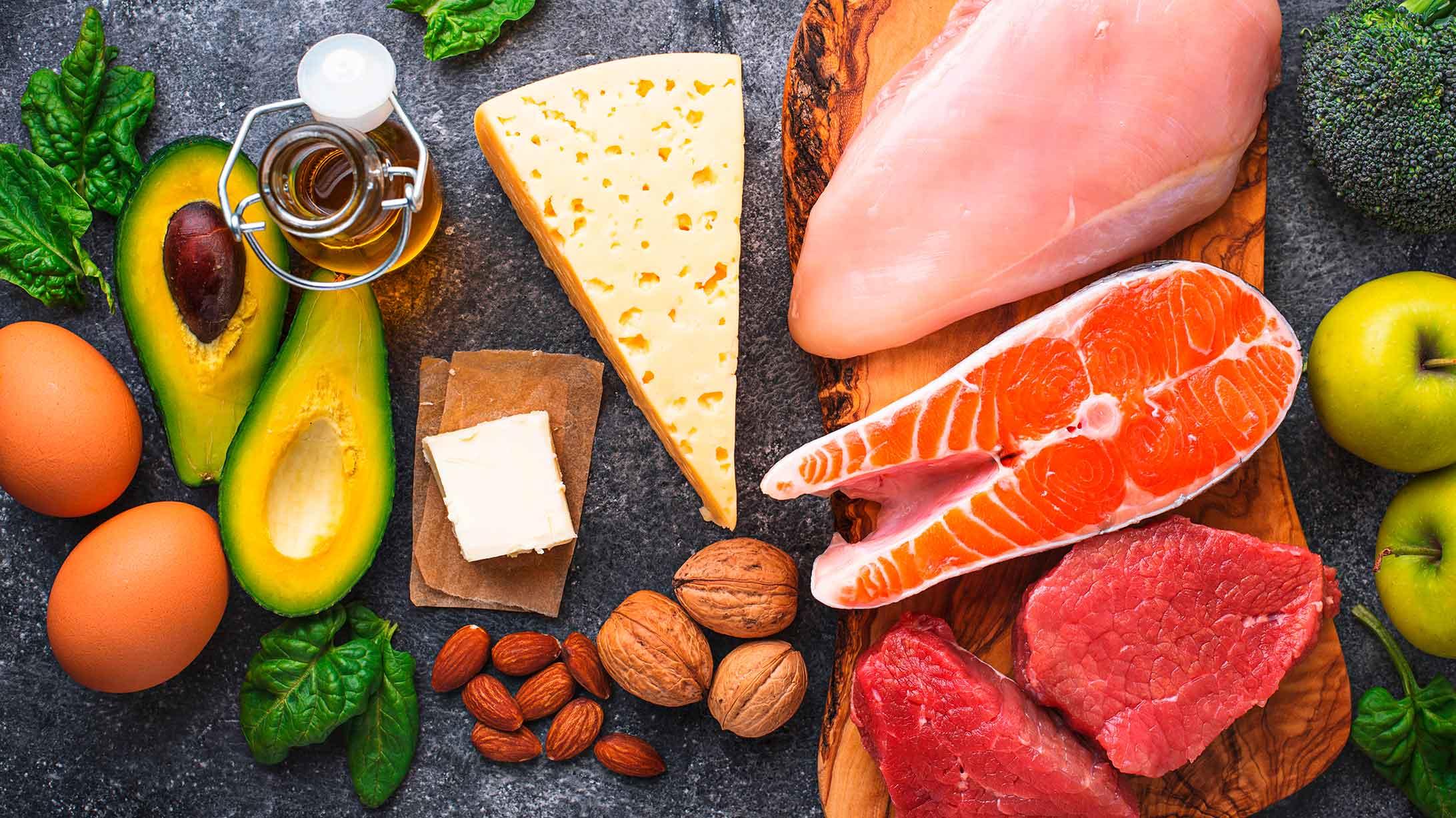 Das Bild zeigt Gemüse sowie Fleisch, Fisch und Nüsse.