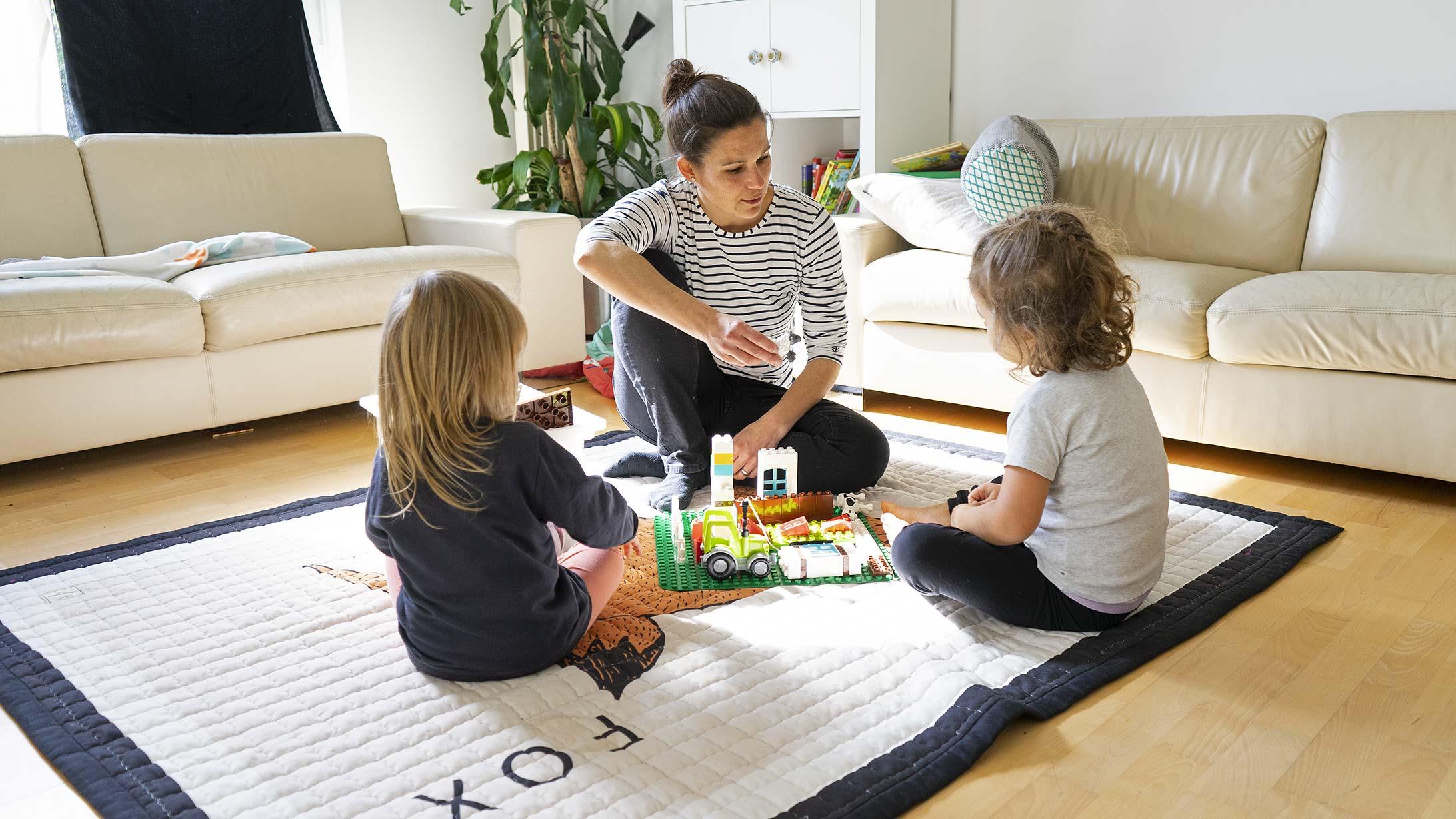 Cordula Peterhans, Lungenkrebspatientin, spielt mit ihren zwei Kindern im Wohnzimmer.
