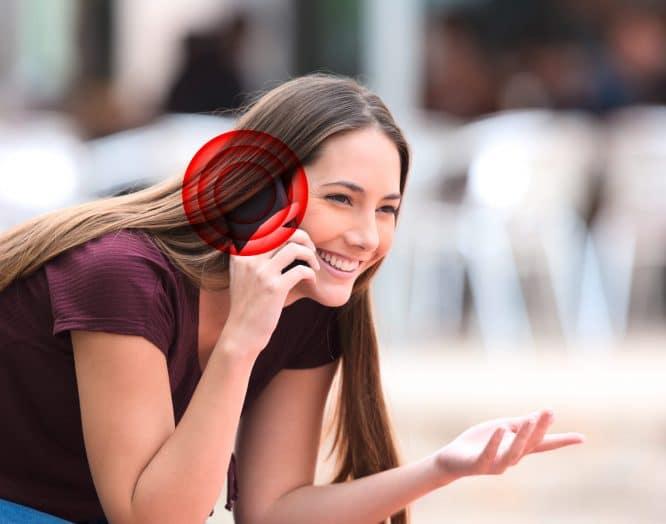 telefonierende junge Dame mit rotem Kreis am Ohr, das Krebs symbolisiert
