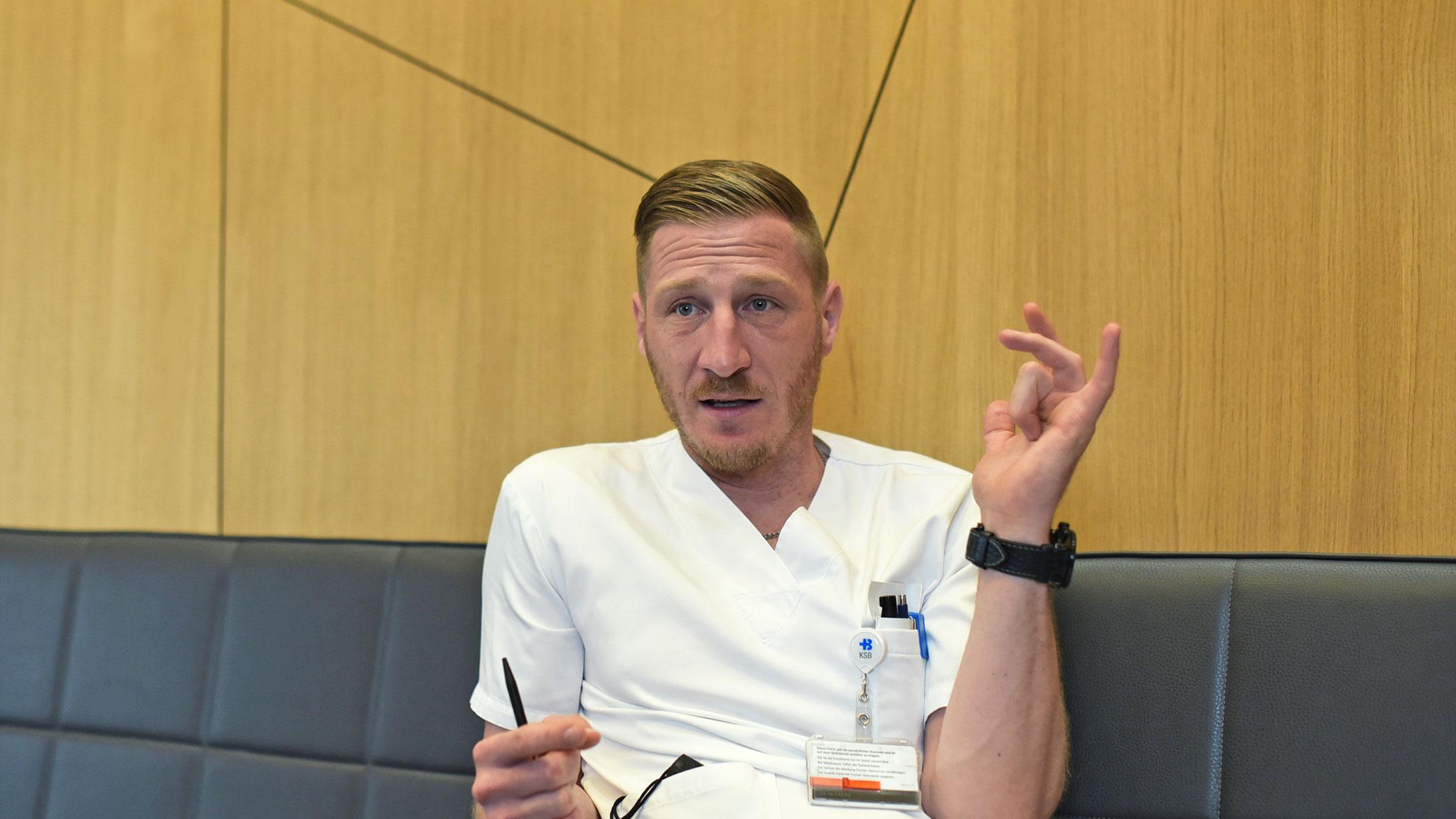 Handchirurg Patrik Schmid demonstriert mit seiner Hand, wie Morbus Dupuytren die Beweglichkeit der Finger einschränkt.