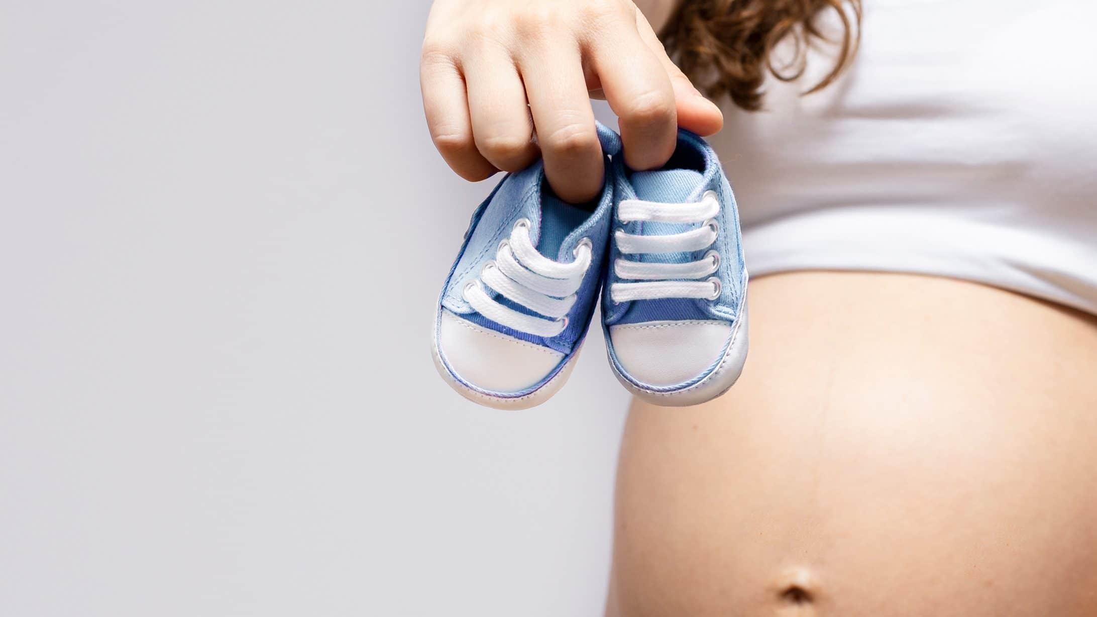 Eine schwangere Frau mit Babyschuhen